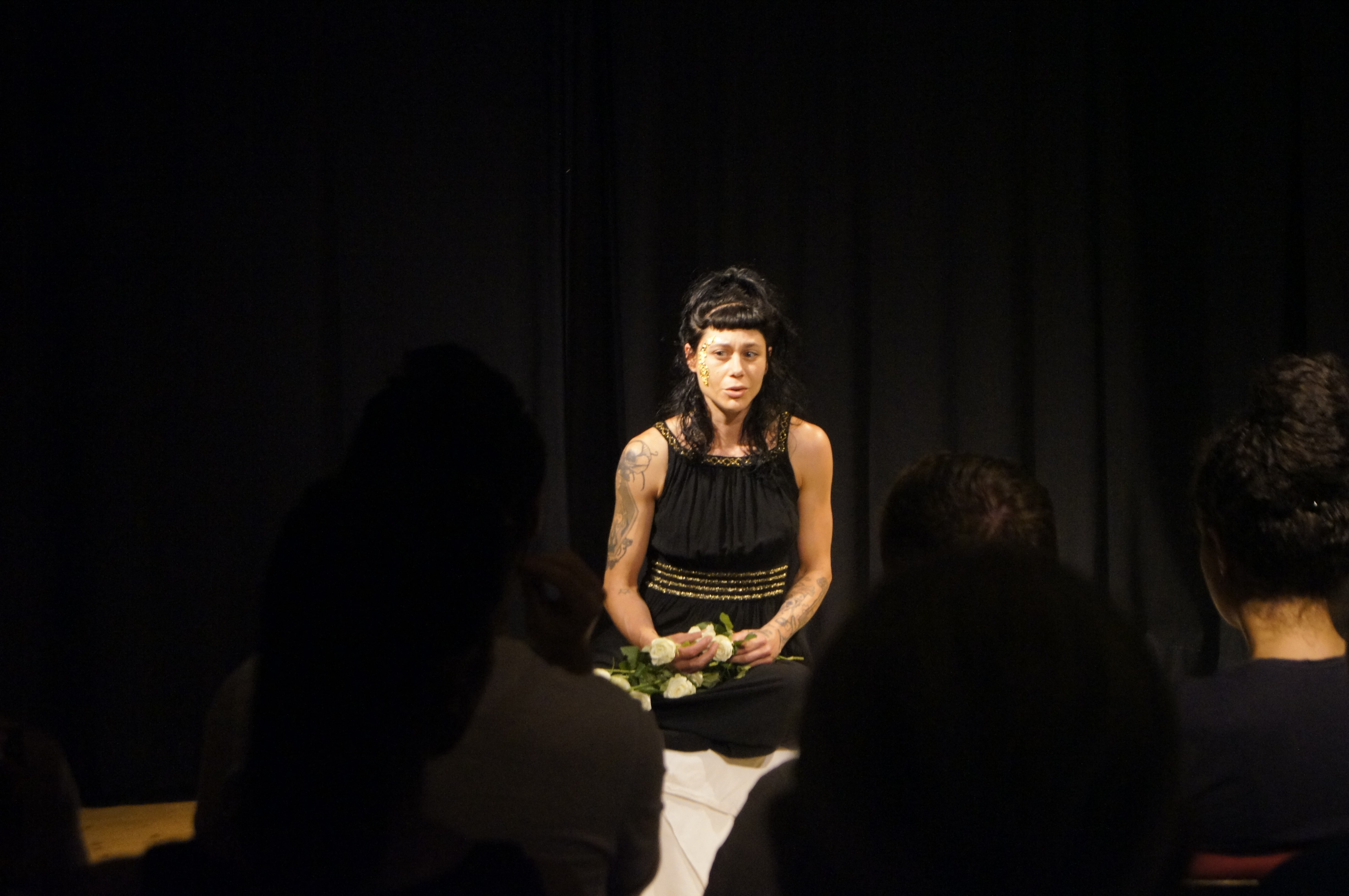 Theatre performance, Woman with dark brown hair, bangs, and a black, ancient Greek-looking dress. Black curtain behind her. She looks worried