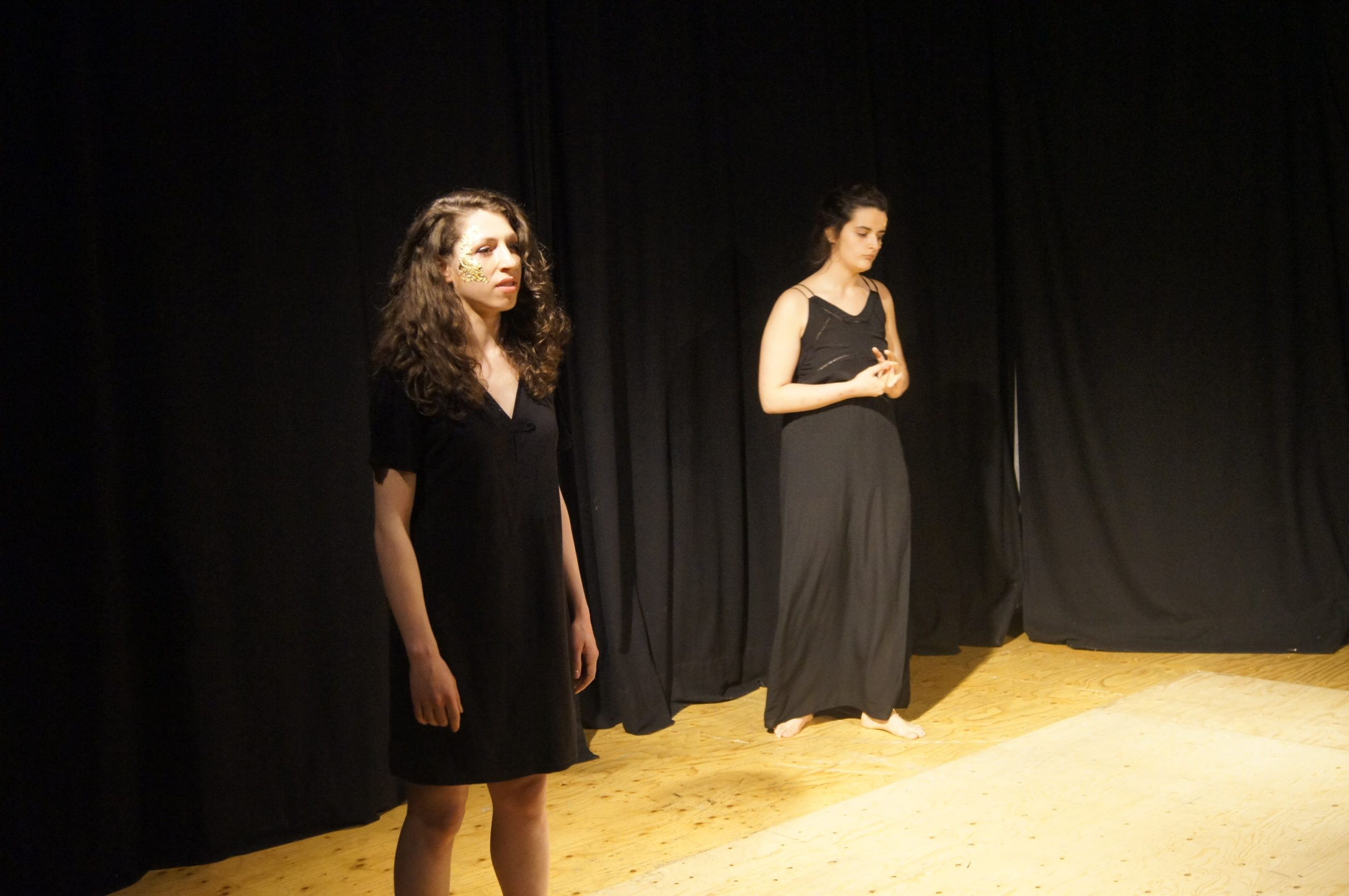 Theatre performance, two women on stage with black dresses. One is reciting, the other one looks sad or concerned