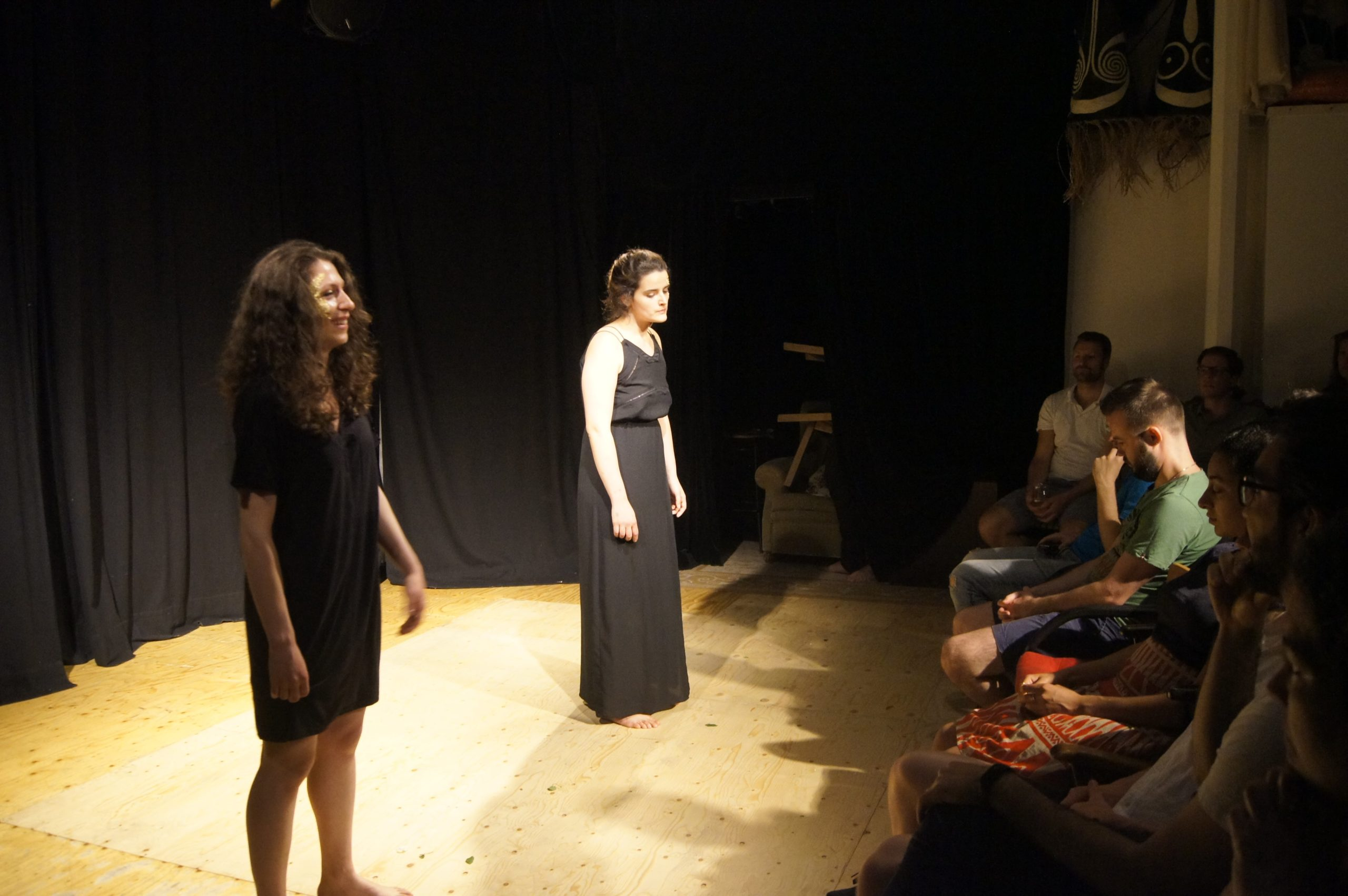 Theatre performance, two women on stage with black dresses, standing in front of audience. One laughs, the other one looks down.