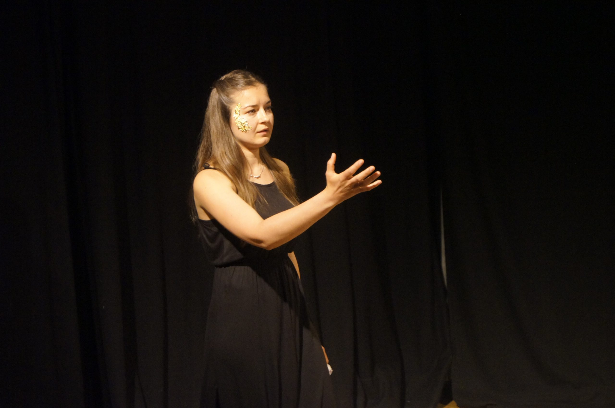 Photo from the theatre performance Keeping up with the Greeks. woman on stage with a black dress, dark blonde hair, golden flakes on her right cheek. Black curtain behind her. She is reciting