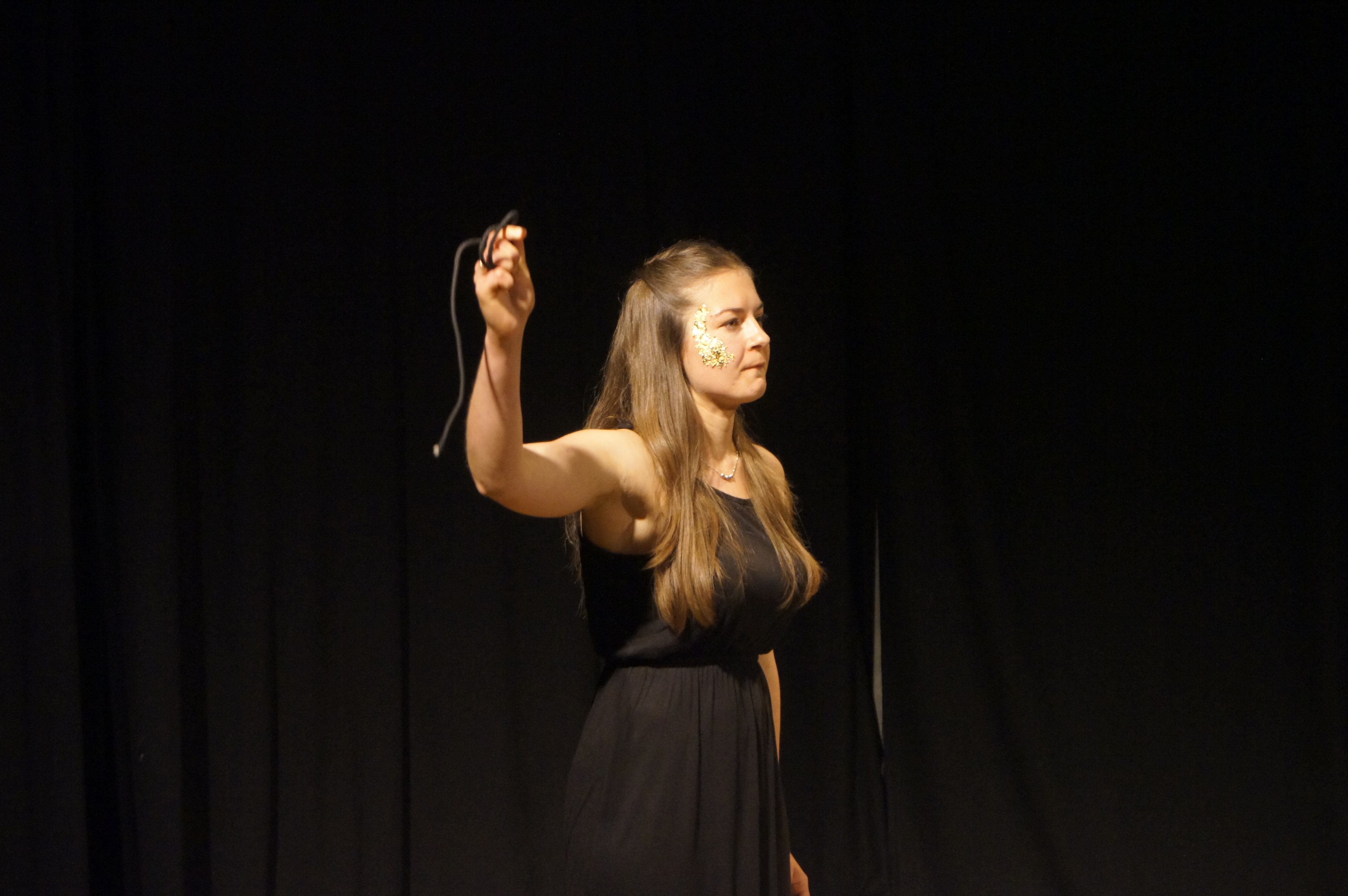 Theatre performance, woman on stage with a black dress, dark blonde hair, golden flakes on her right cheek, holding a string. Black curtain behind her. She looks angry