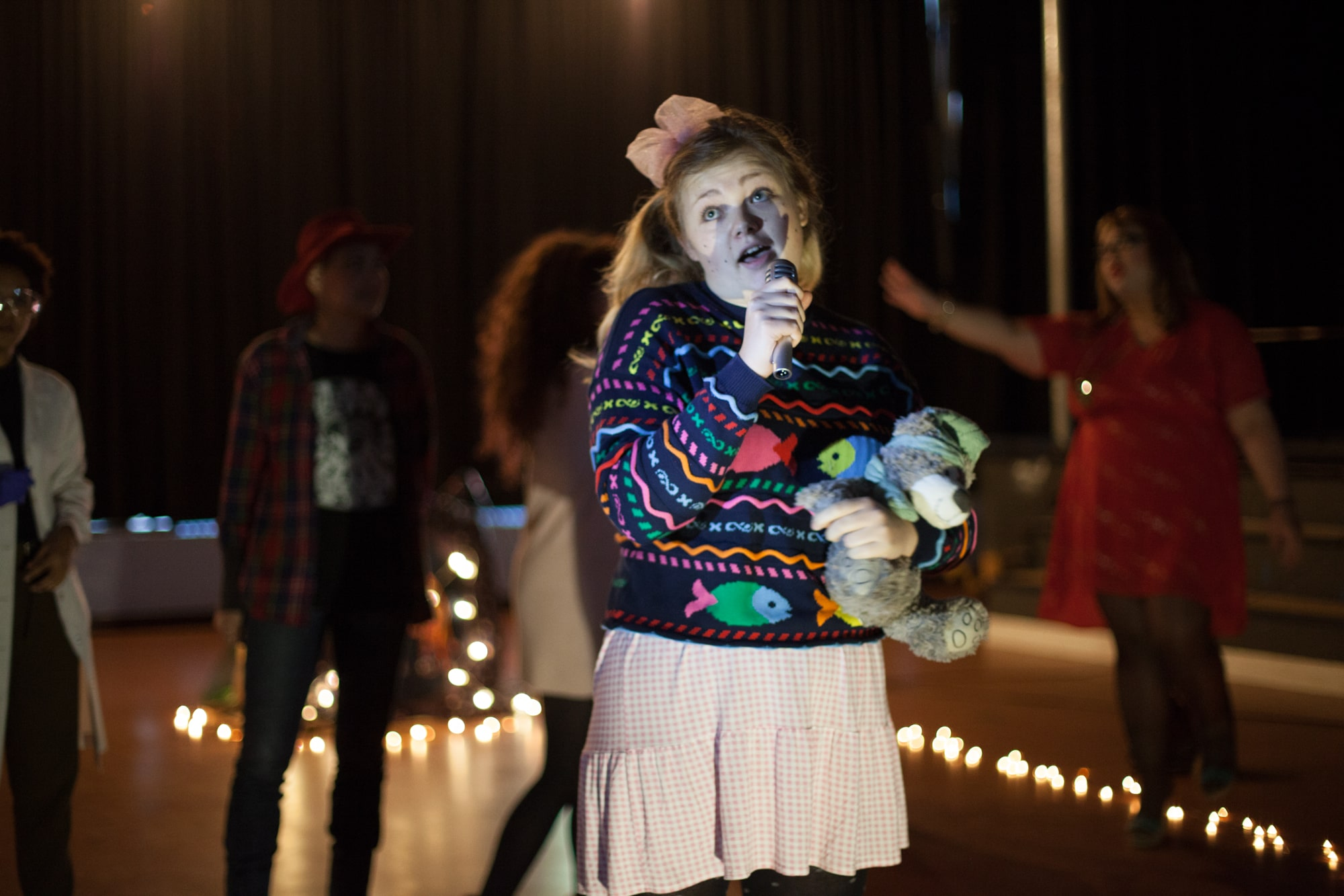 Act Attack theatre class performing girl in her 20s blonde hair dressed like a baby girl holding microphone