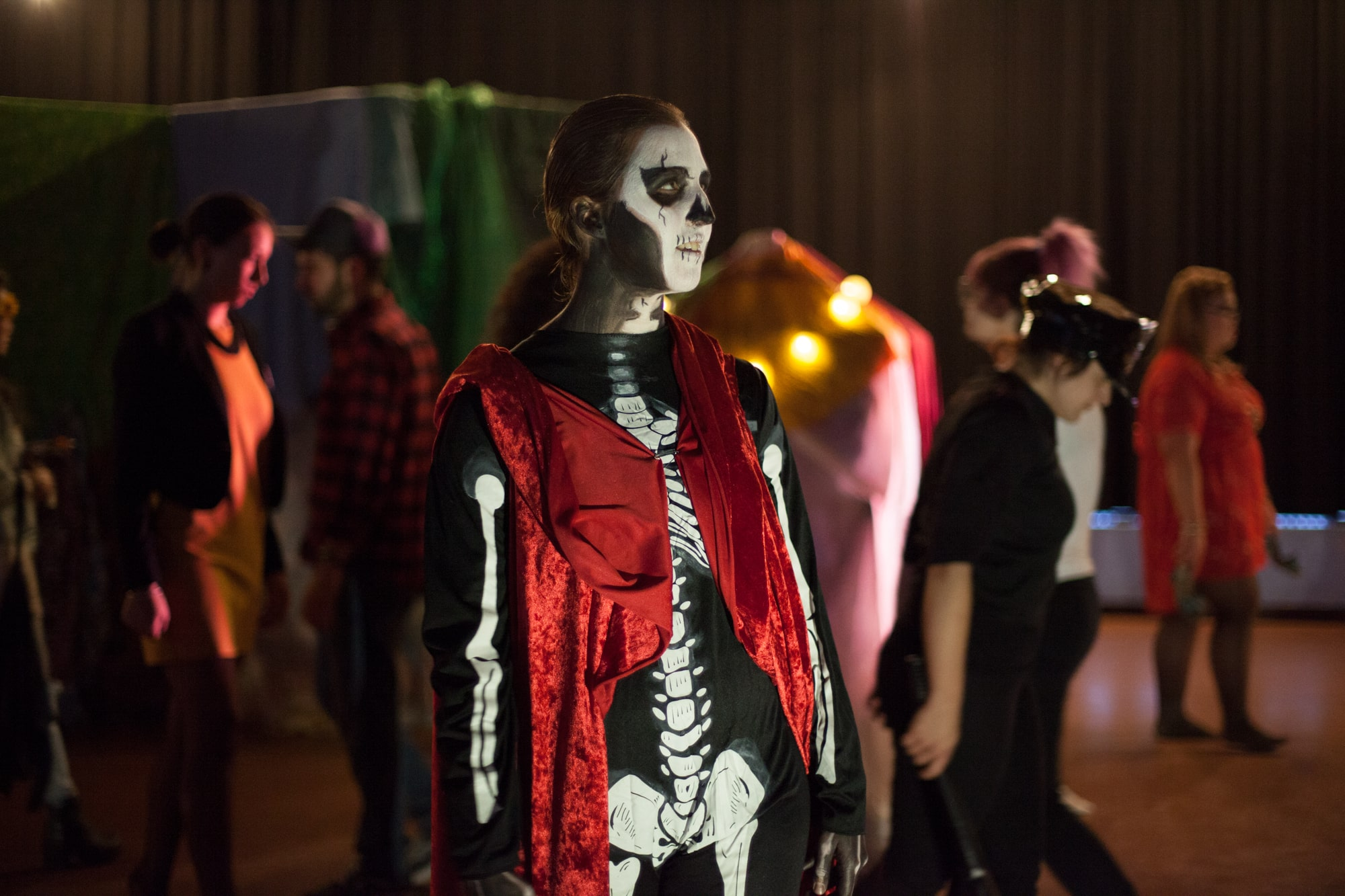 Act Attack theatre class actors performing. Woman with dark long hair dressed in a skeleton costume and red cape