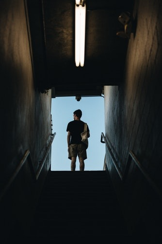 Actor at the top of stairs, inside a tunnel. He's looking out.