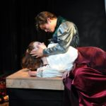 Theatre performance of the shy actor. Man is crying looking at woman, she is unconscious. They both wear medieval clothes