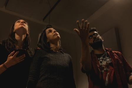 three actors looking up and beyond the photo. One of them is pointing with his arm open. One man and two women