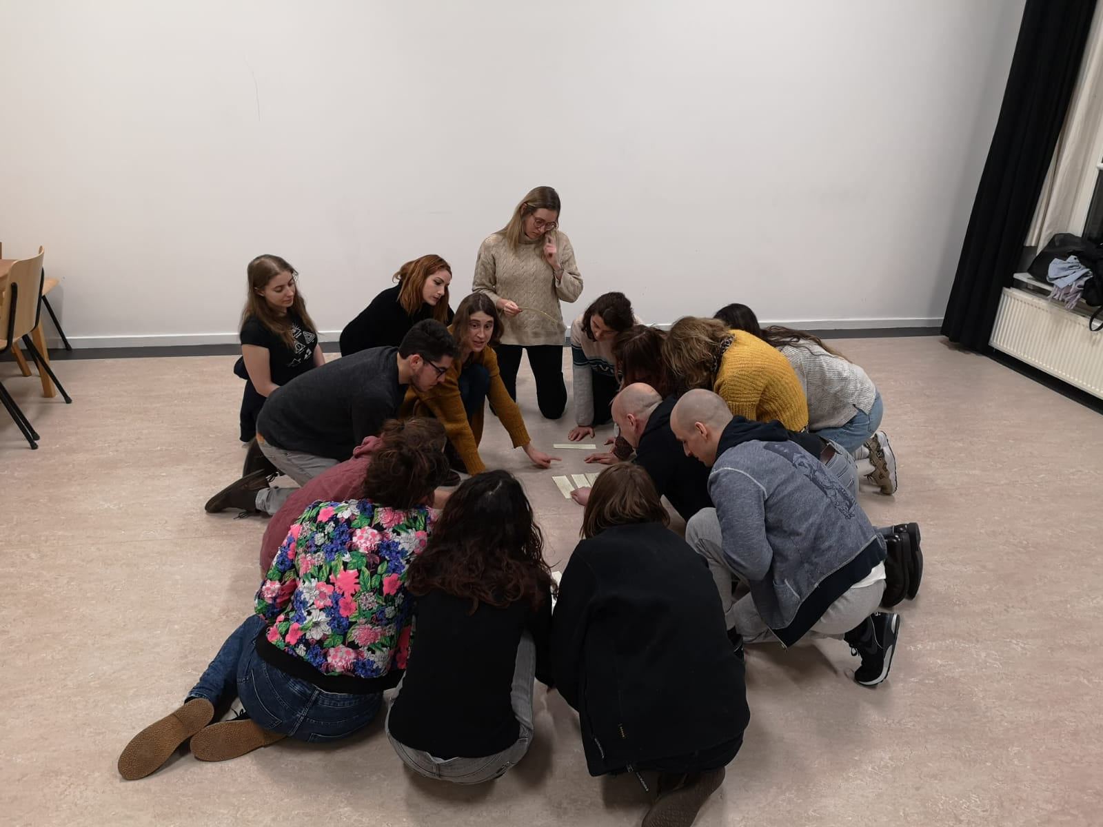 Acting Class Act Attack. A group of people form a circle, sitting on the floor, looking at some notes they have laying on the ground