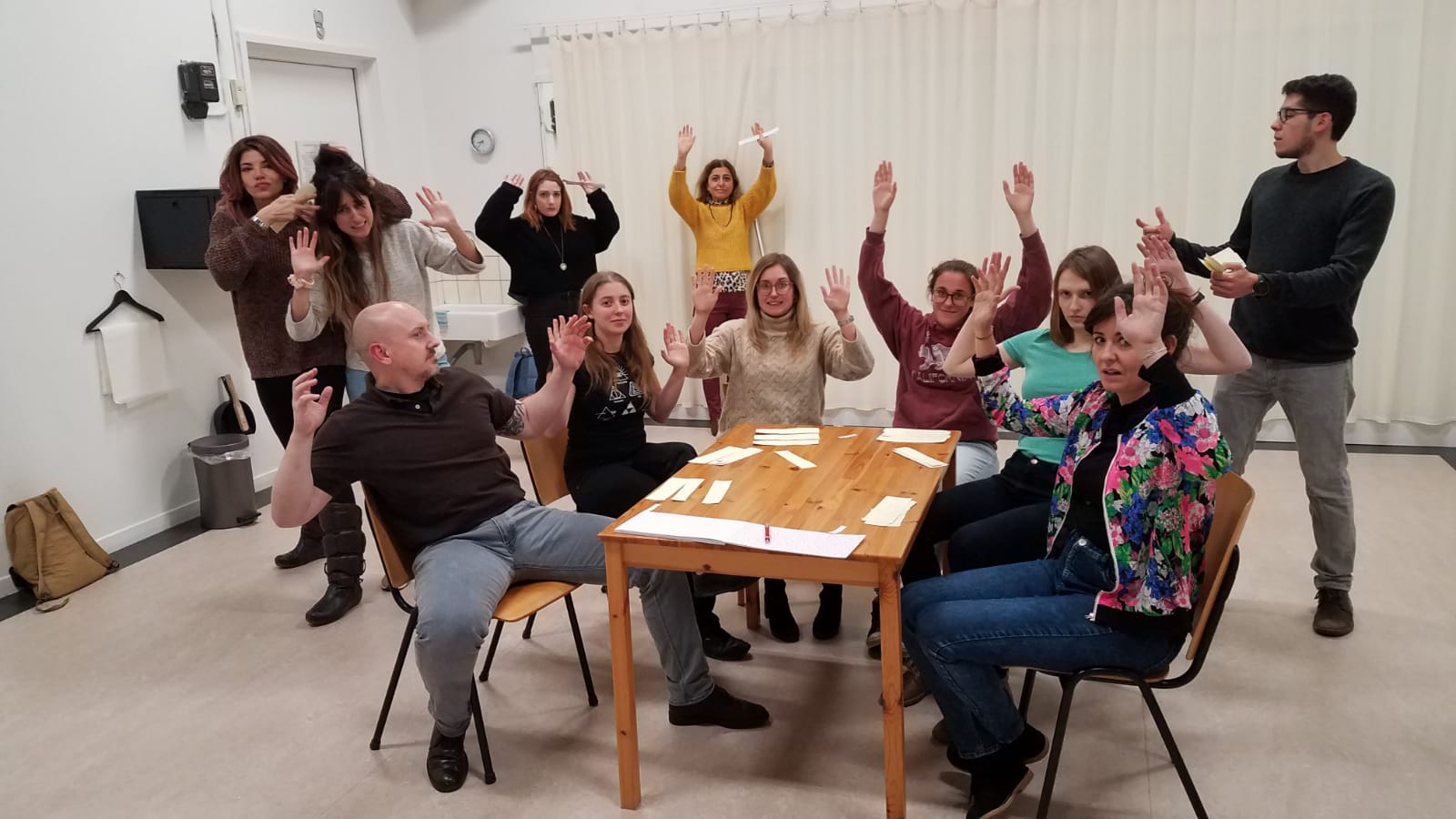 Acting Class Act Attack. A group of people form a semi-circle around a square table. Some are standing behind them. They all have their arms up in the air