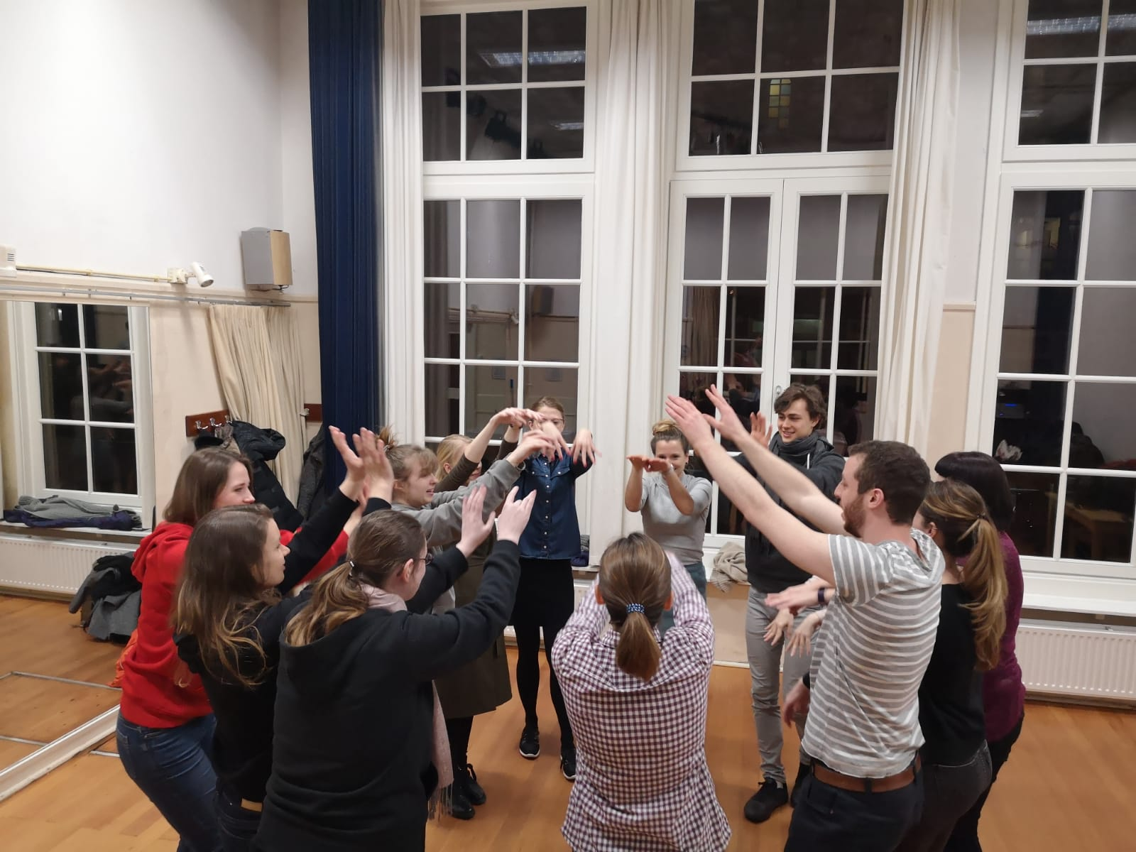 Improv Class Act Attack. A group of people are standing in a circle, with their arms up in the air and reaching towards the centre of the circle