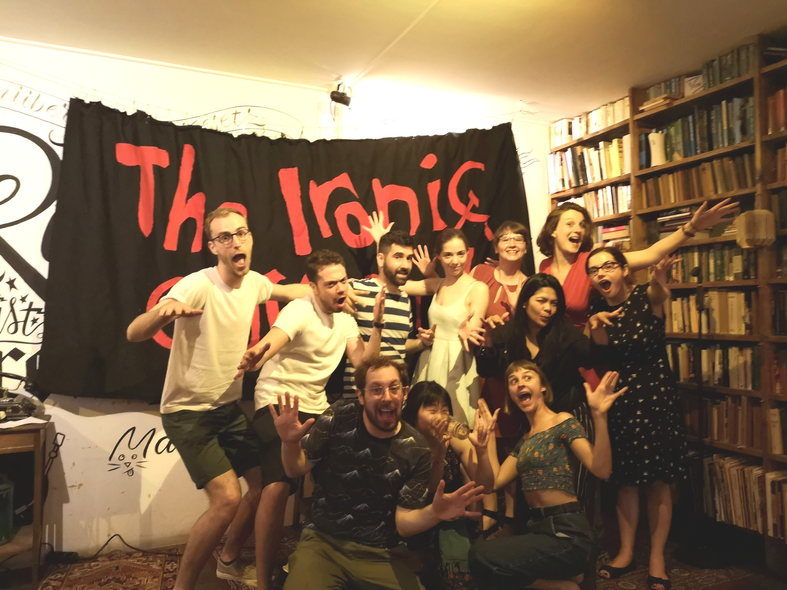 A group of people poses for the picture. Behind them there is a black banner with red letters and a library.