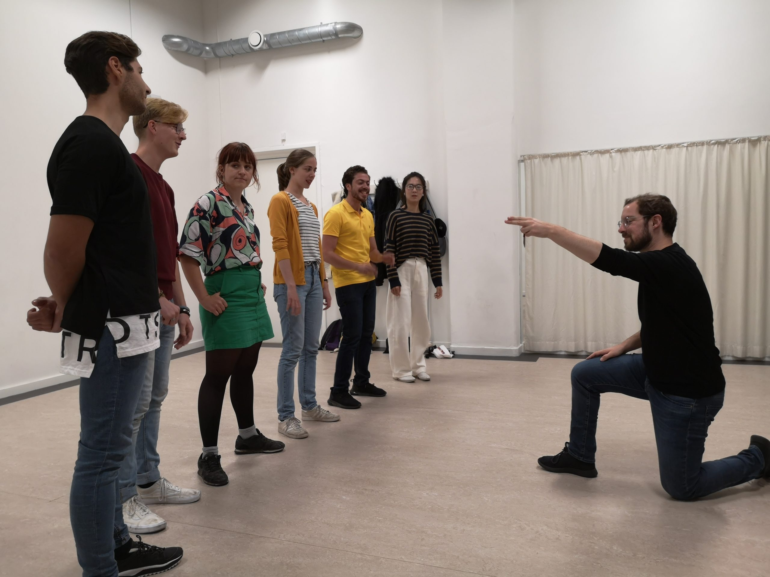 Pure improv for beginners class. A group of people stand in a row. One man is on one knee pointing one of the others, like he's holding a gun.