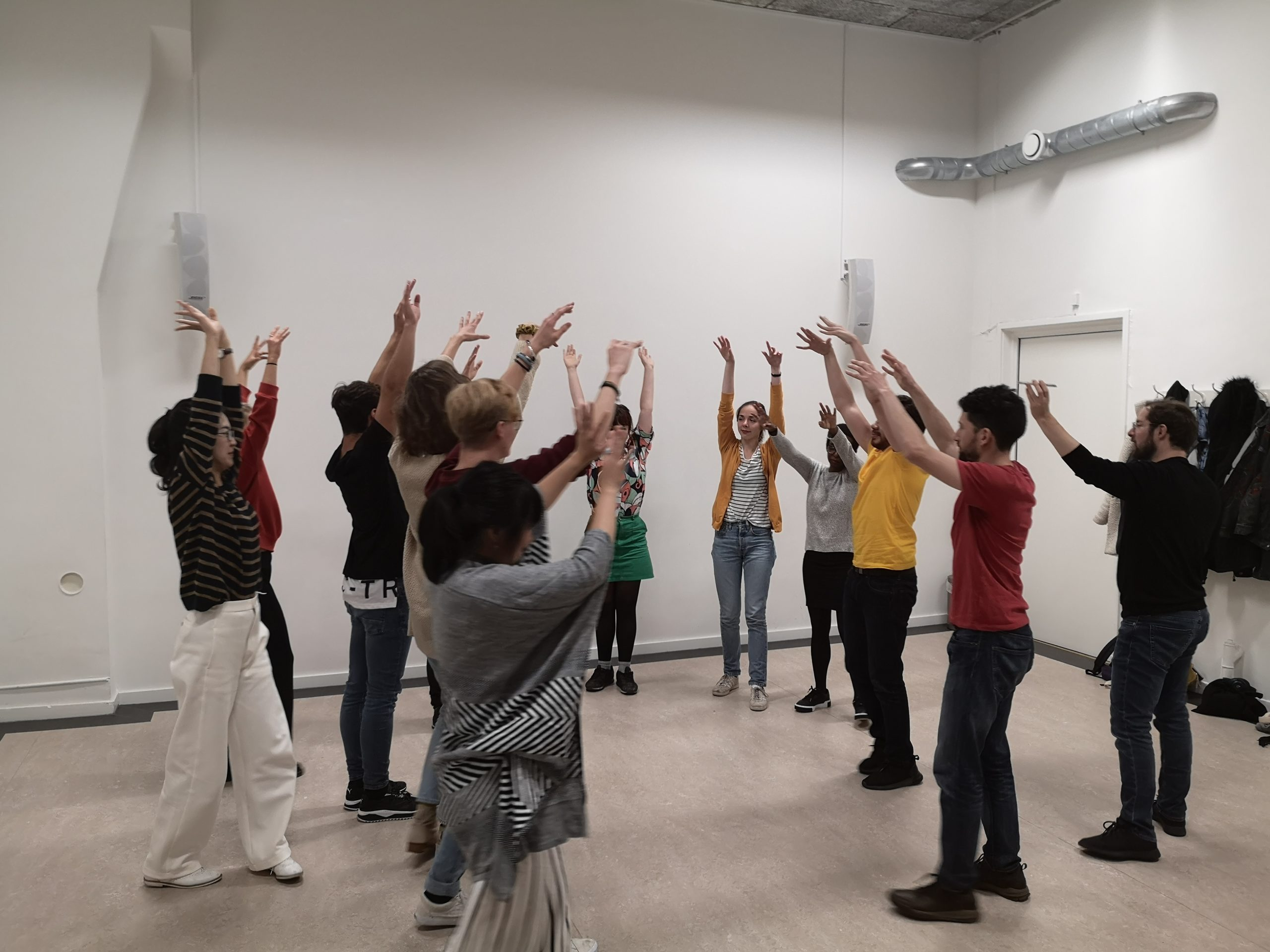 Pure improv for beginners. A group of people form a semi-circle holding their hands up in the air.