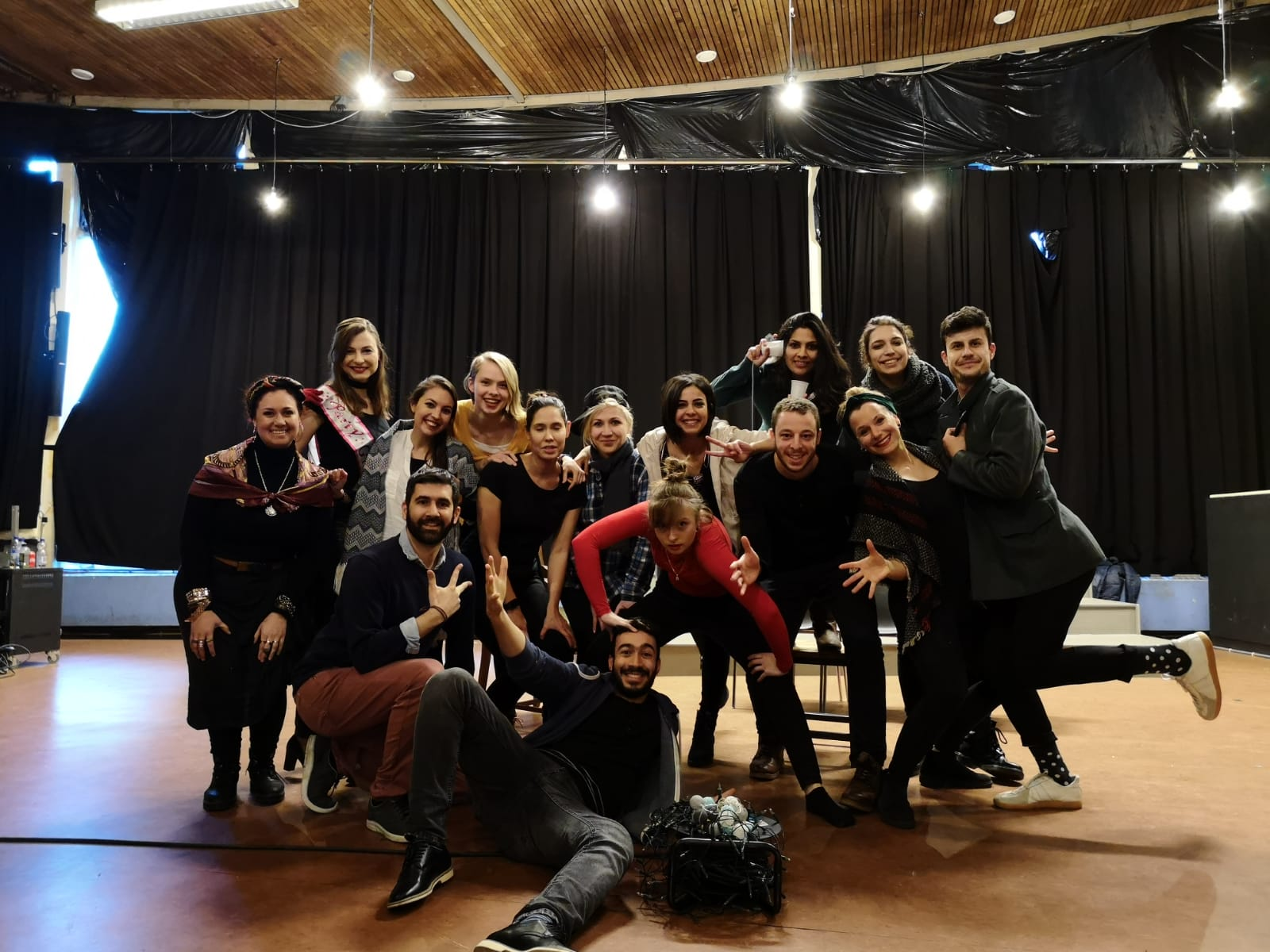"Photo from the show ""The Skin of our Teeth"". A group of people pose for the picture. Most of them wear black. At the back, there is a black curtain"