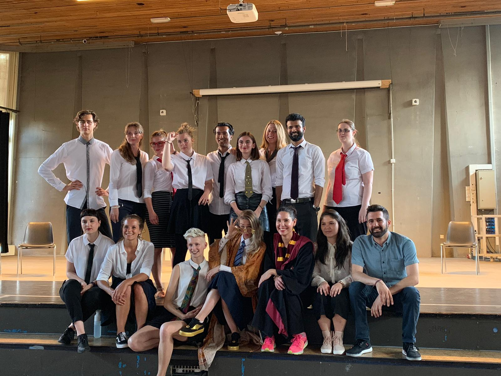 "Photo from the rehearsal of the show ""the magic school"". A group of people pose for the picture. Most of them wear a white shirt and tie"