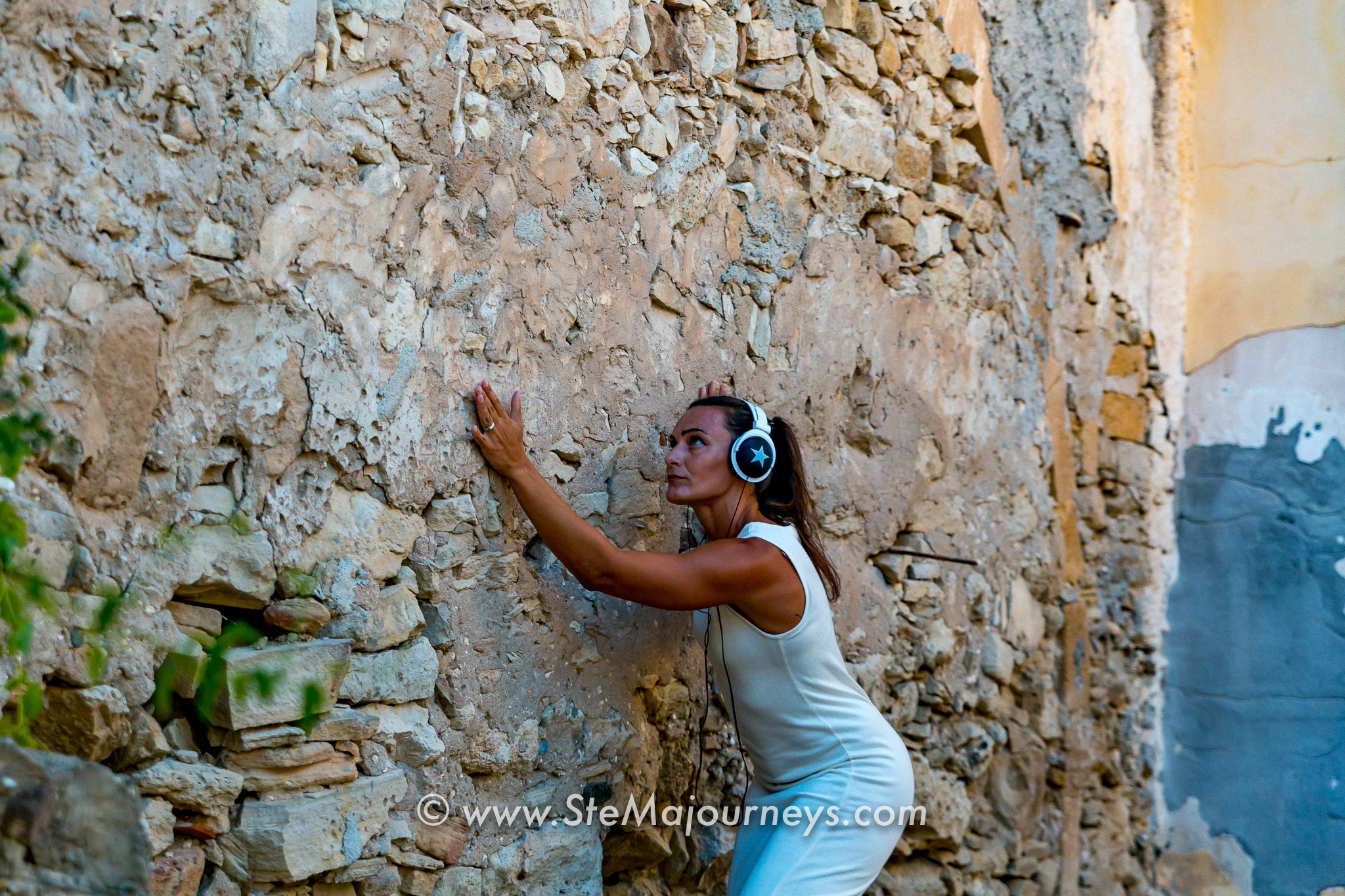 A woman (white dress, long brown hair, headphones on) is touching a stone wall that seems to be in the Mediterranean