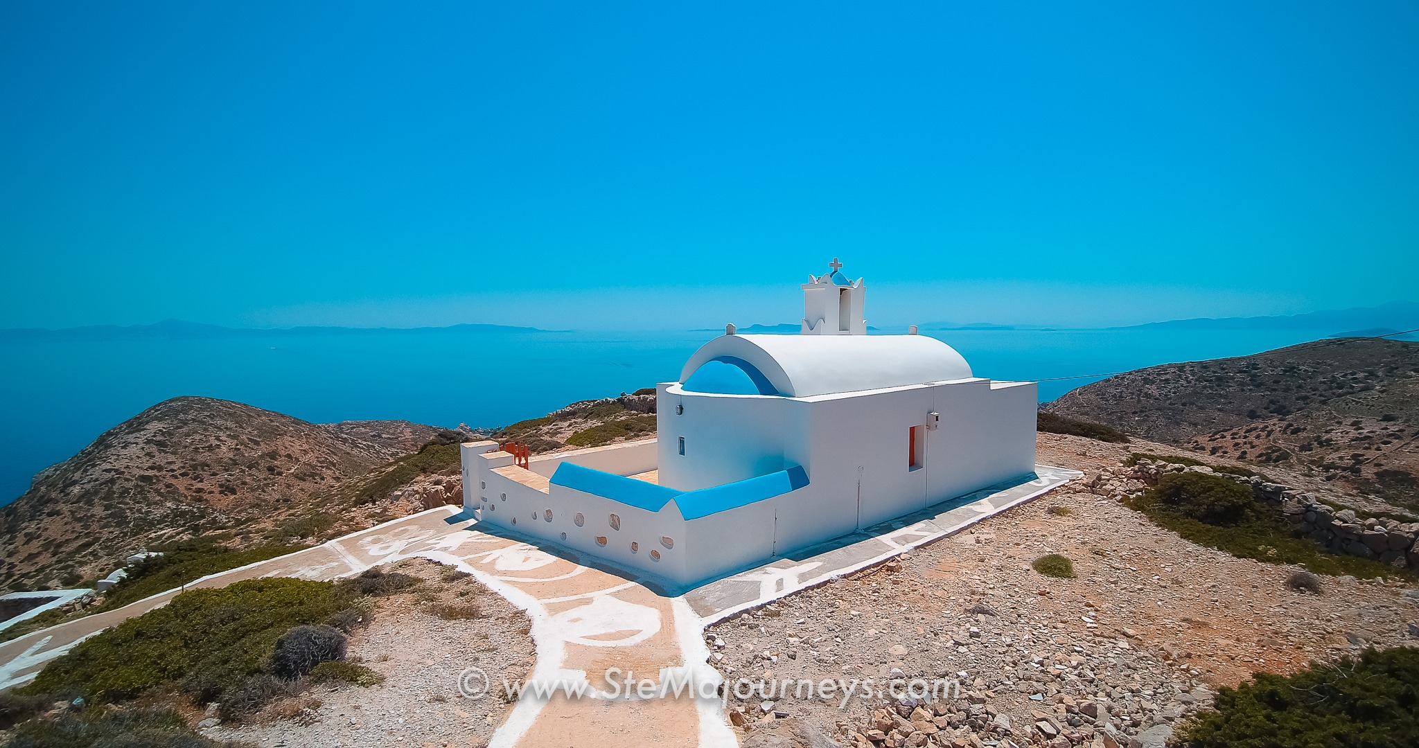 View of a church on the Aegean sea. The church is white and blue, built on a hill. The surrounding nature is dry. The ocean is in the background