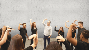 Actors practicing. A group of people wearing black, except for one man with glasses wearing a white shirt, have their arms lifted in a 90 degree angle with their wrist also in a 90 degree angle. Background: Grey brick wall