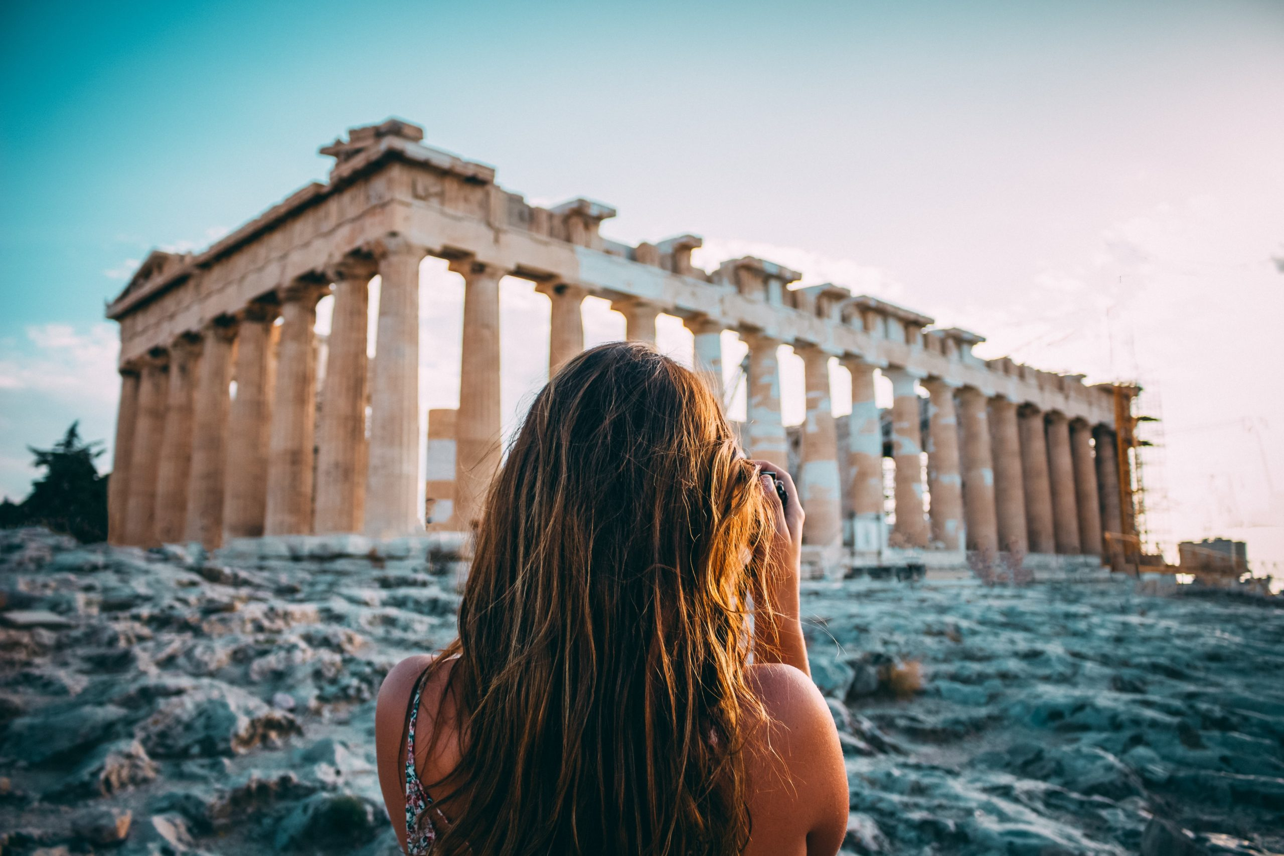 Backside of a woman with brown hair who is taking a picture of the temple of Parthenon