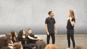 Actors practicing. A group of people sitting on the floor wearing black. A guy and a girl are standing talking to each other. Background: Grey brick wall