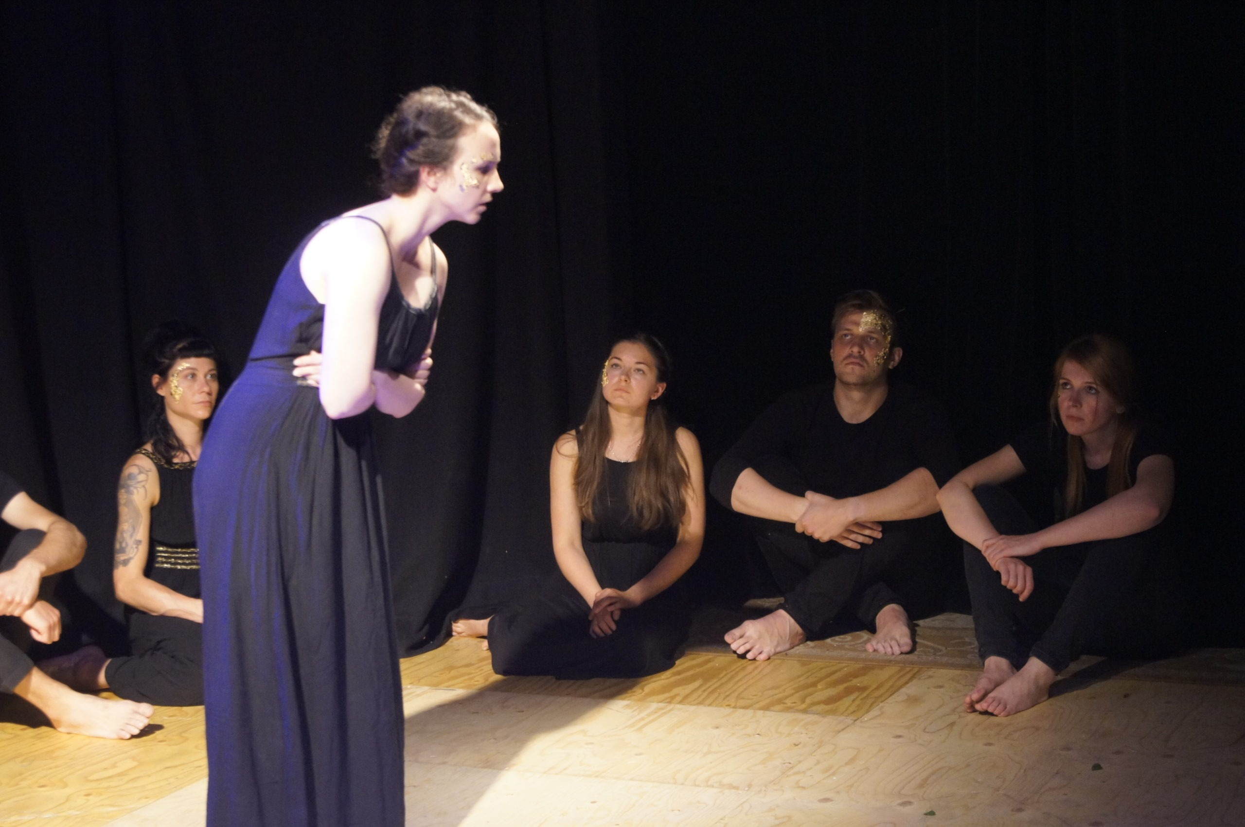 Photo from the theatre performance Keeping up with the Greeks. Woman on stage with a black dress, brown hair, golden flakes on her right cheek, holding her stomach. Behind her, four actors on the floor, black clothes, golden flakes on their face
