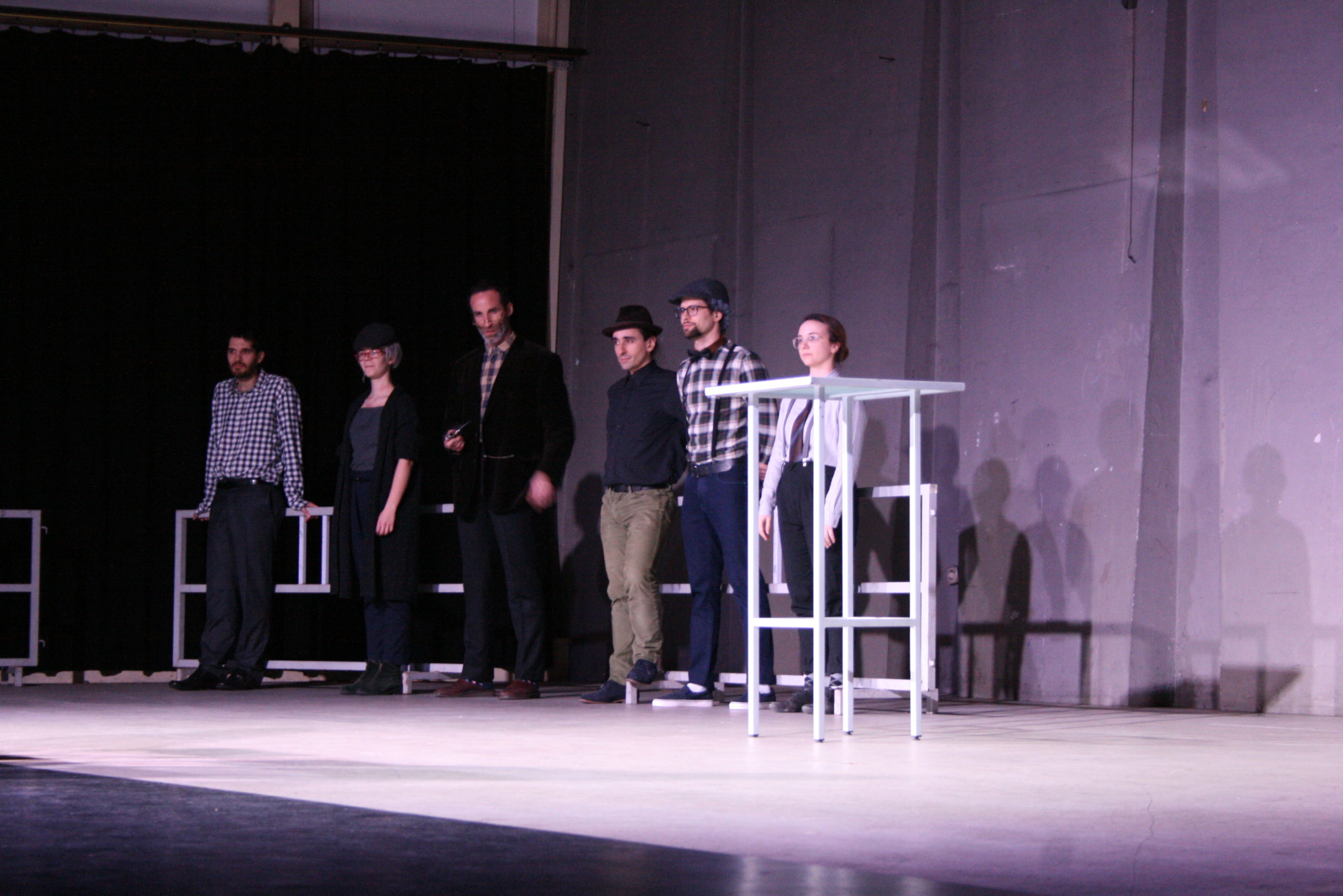 "Photo from the show ""The Chairs"". Six actors stand on stage, wearing old-fashioned clothes, like blue plaid shirts and caps."