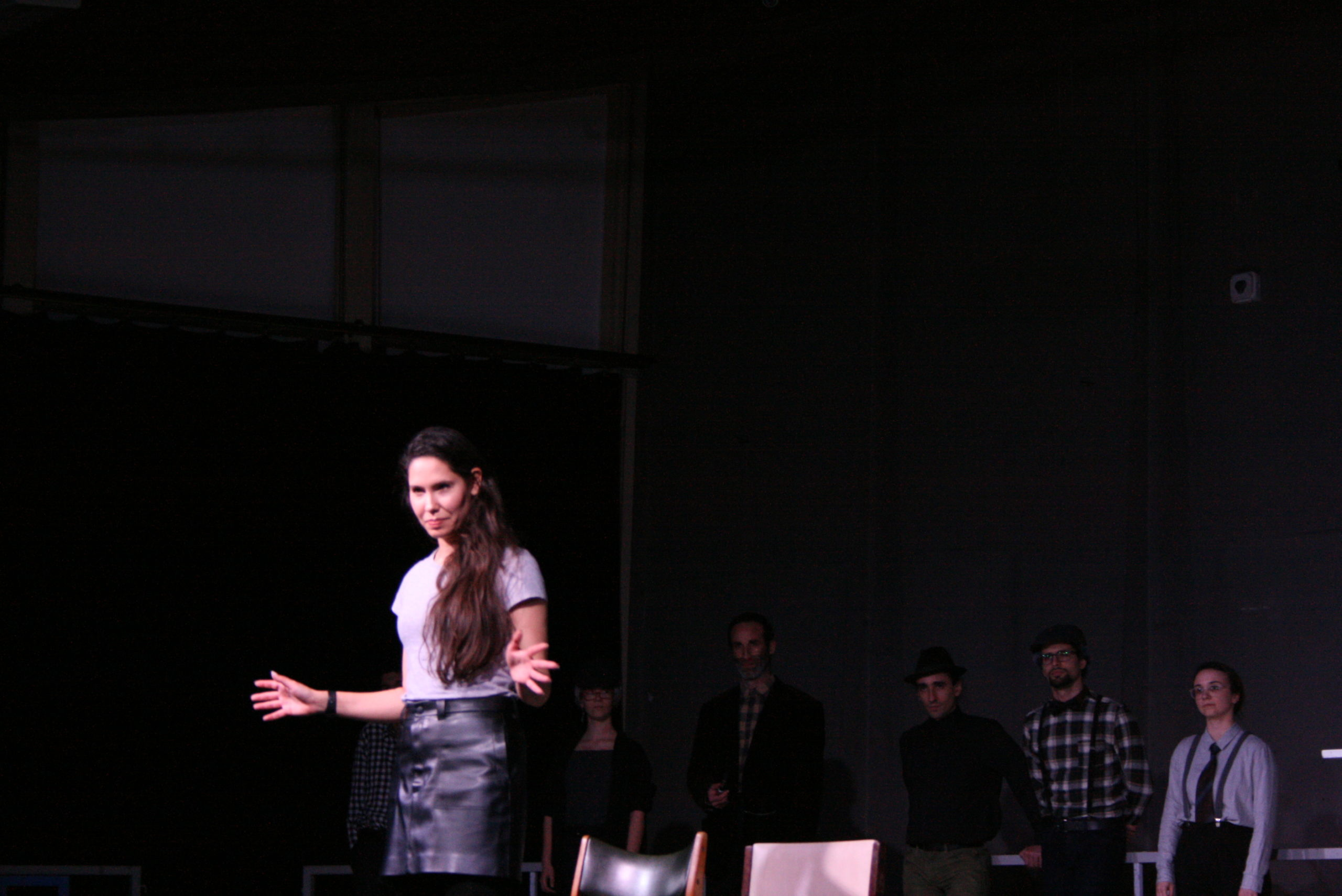 "Photo from the show ""The Chairs"". Six actors stand at the back of the stage, wearing old-fashioned clothes, like blue plaid shirts and caps. A female actor stands at the front, doing jazz hands"