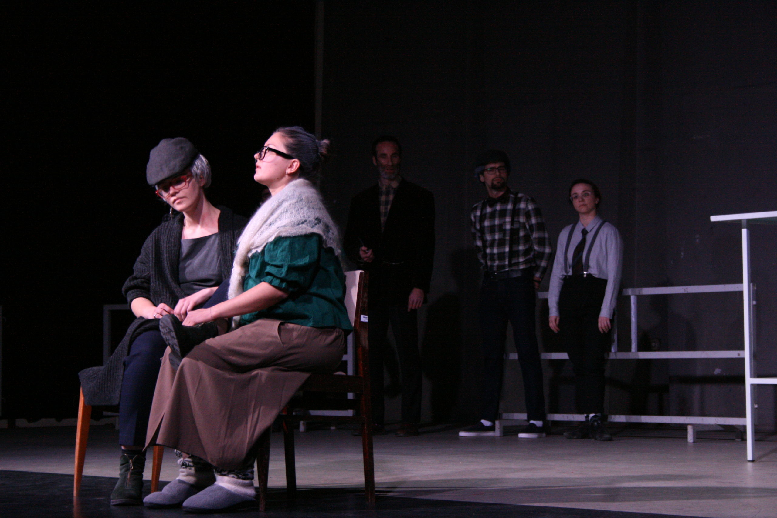 "Photo from the show ""The Chairs"". Three actors stand at the back of the stage, wearing old-fashioned clothes, like blue plaid shirts and caps. Two female actors sit on chairs at the front, dressed like old ladies"