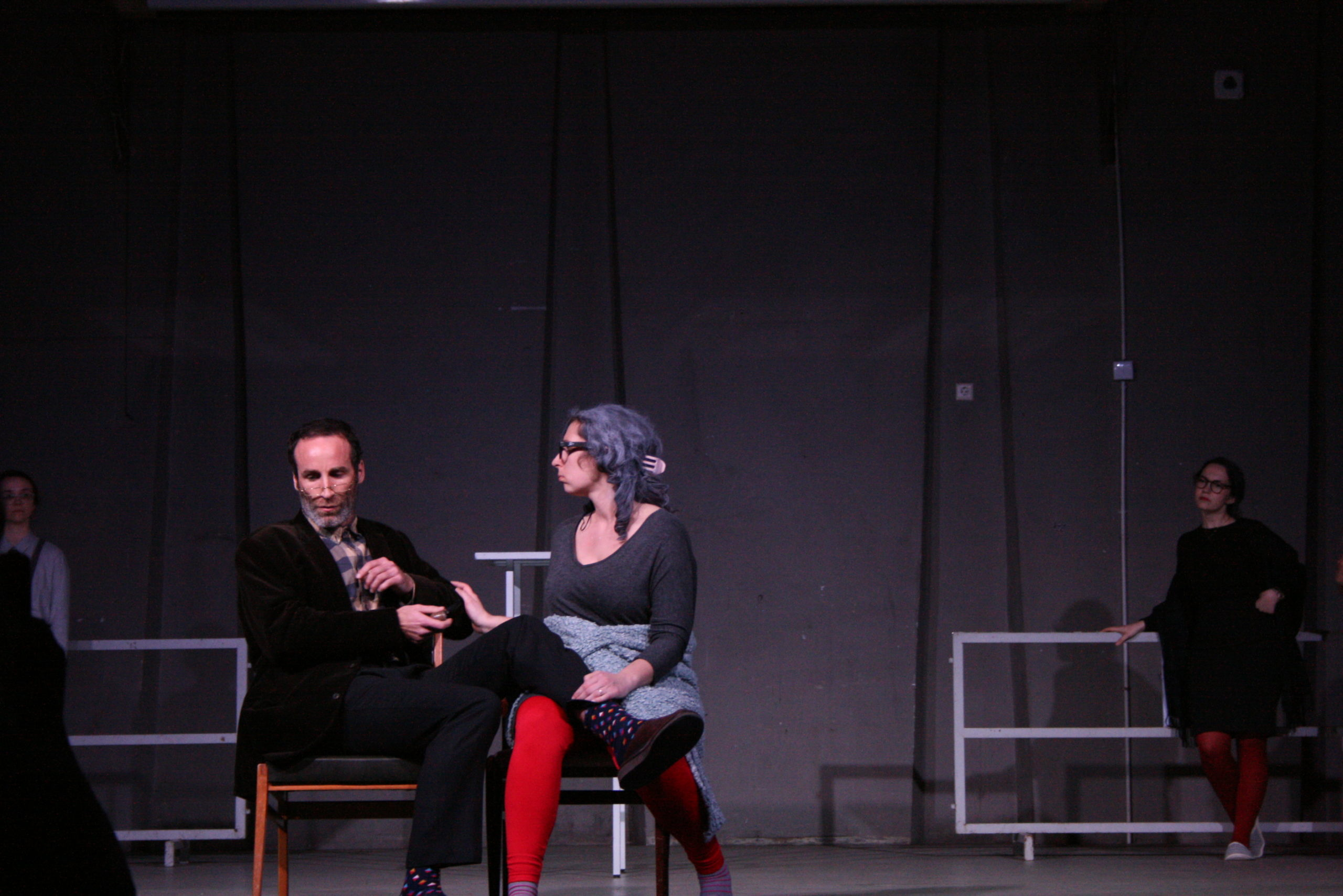 "Photo from the show ""The Chairs"". A male and a female actor sit on chairs. He has his right leg laid on her lap and she is touching his arm"