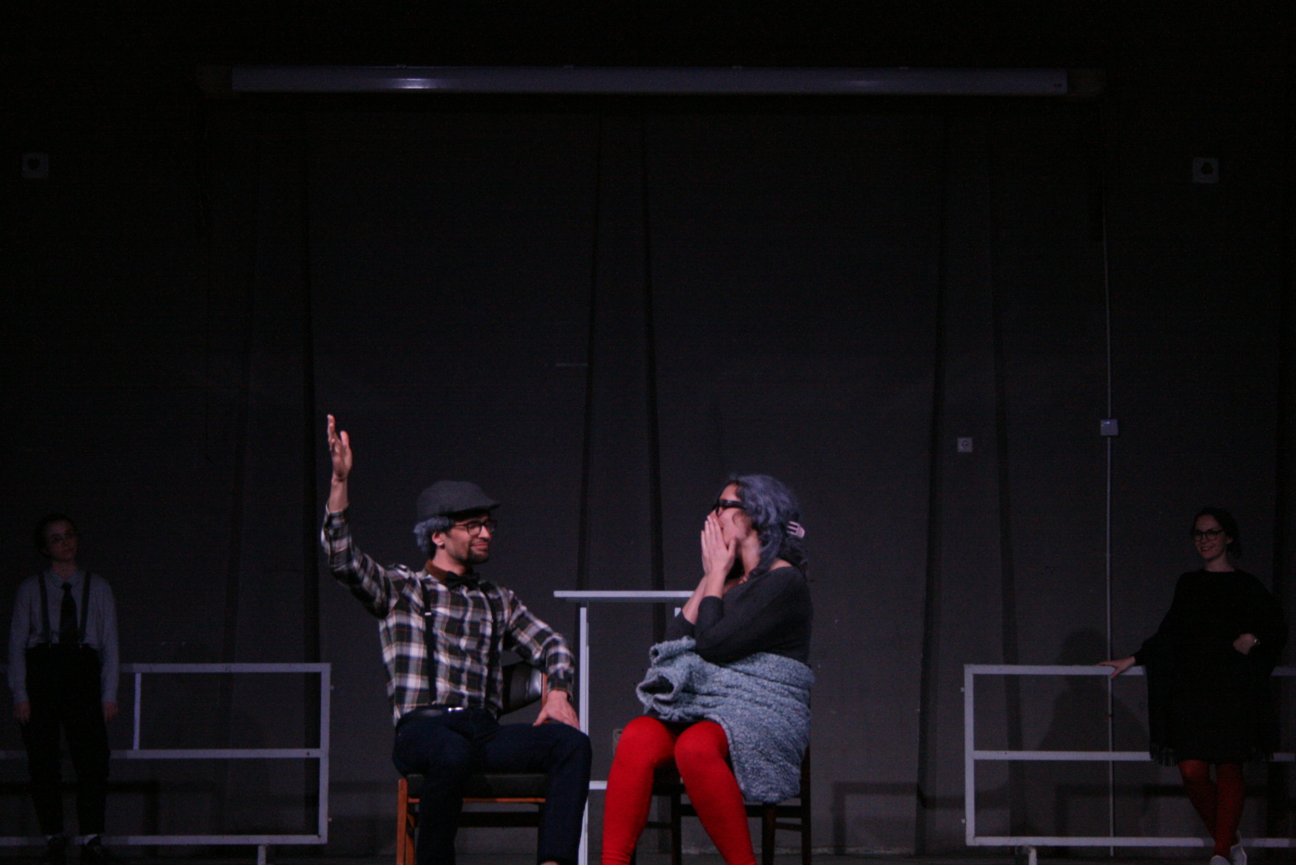 "Photo from the show ""The Chairs"". A male and a female actor sit on chairs. He has is right arm up and she is touching her face in shock"