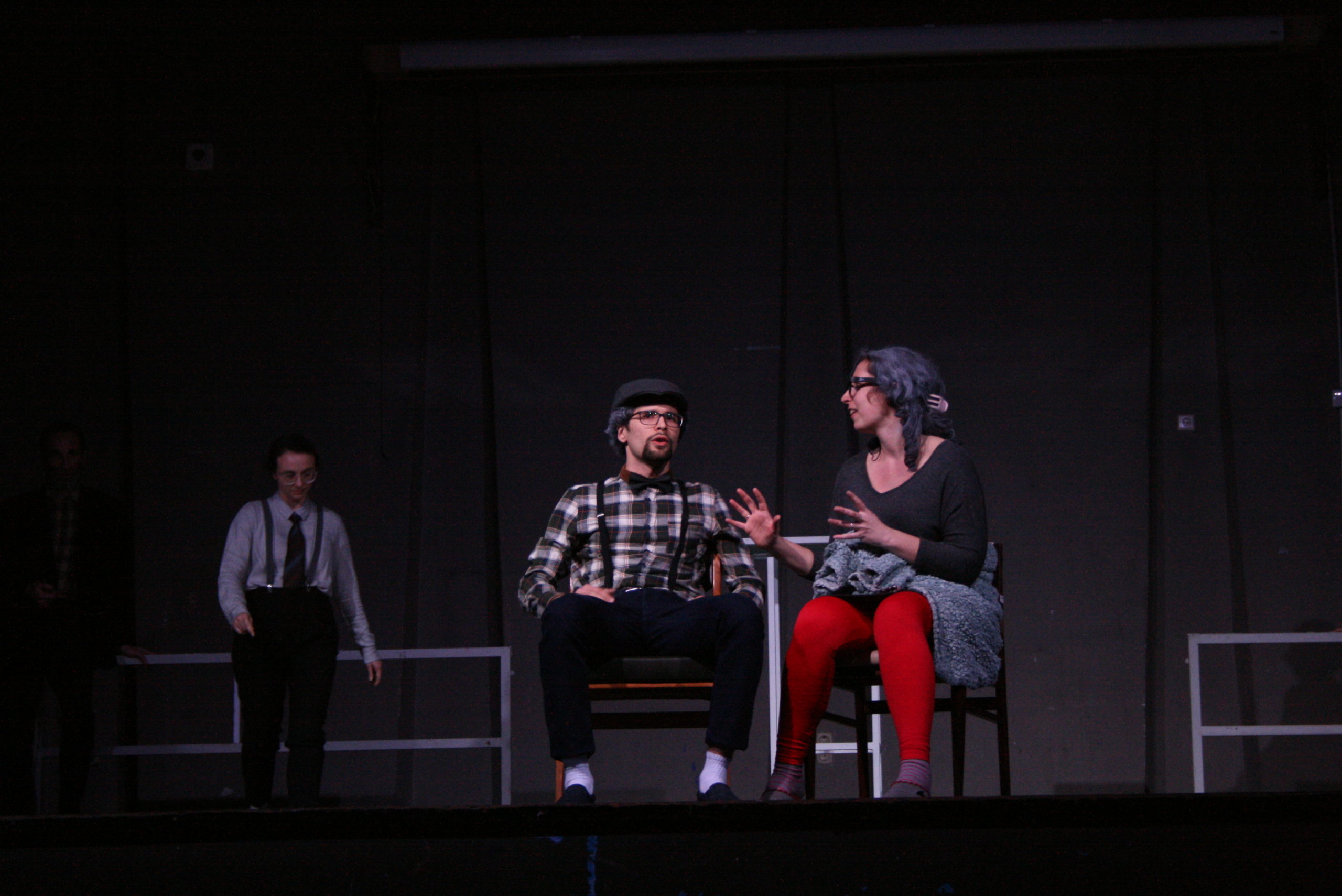 "Photo from the show ""The Chairs"". A male and a female actor sit on chairs, talking. He looks over the audience and she looks at him, her arms open like holding a ball"