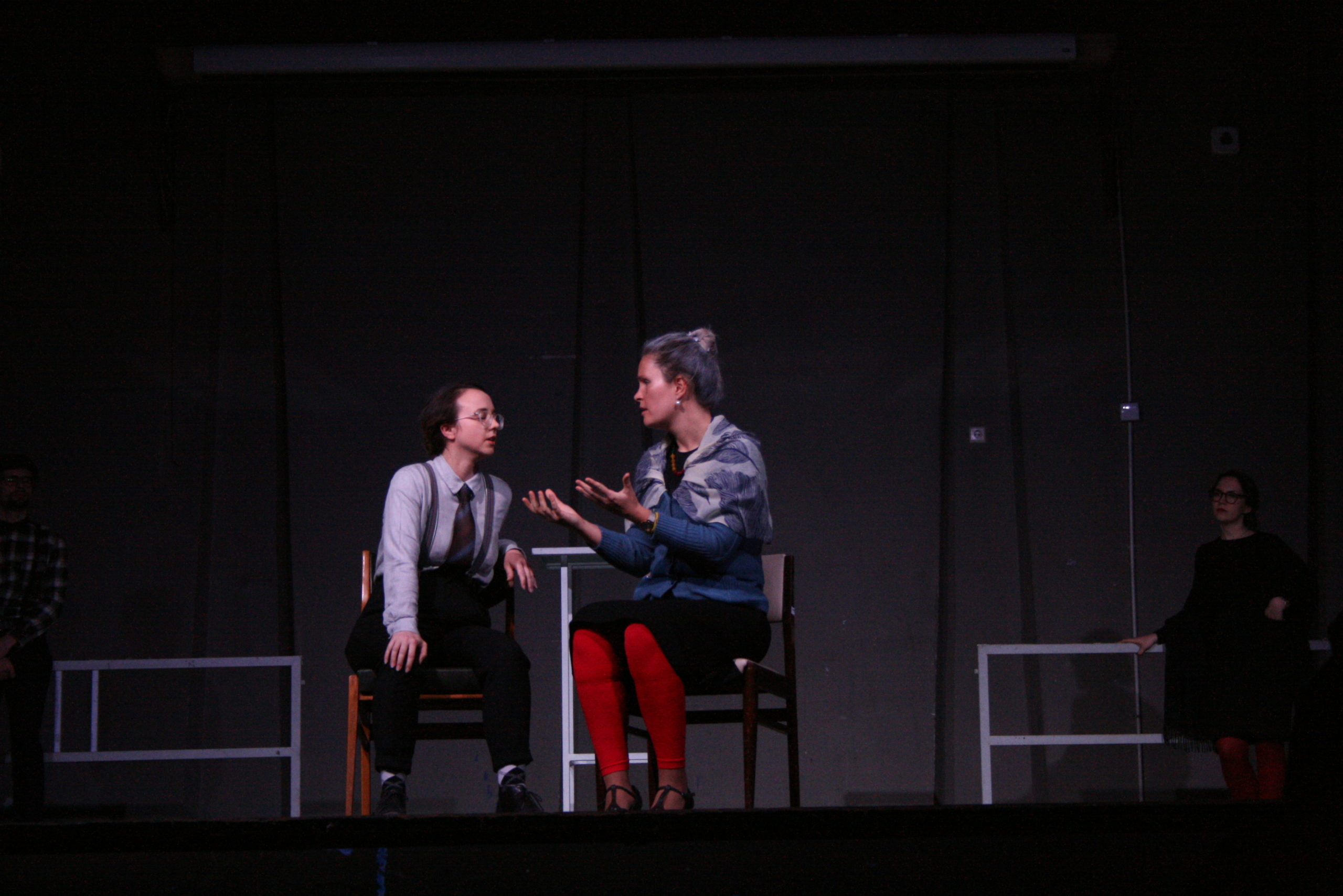 "Photo from the show ""The Chairs"". Two female actors sit on chairs, talking, one of them dressed as male."