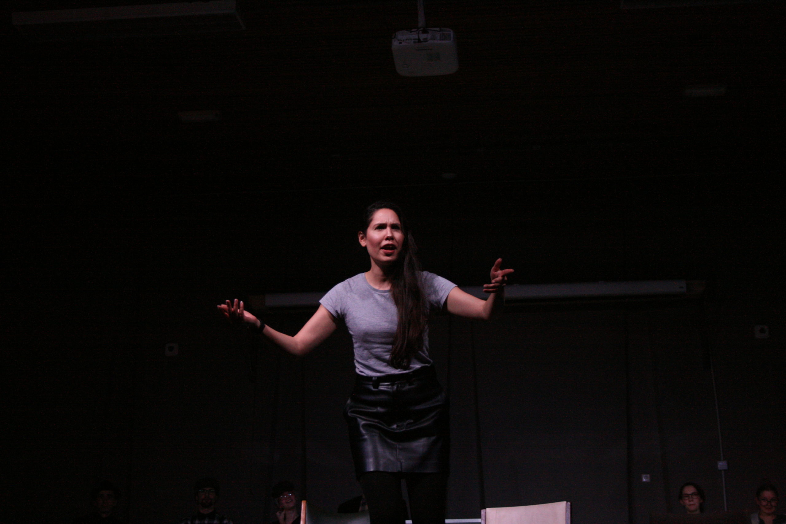 "Photo from the show ""The Chairs"". A female actor addresses the audience. She looks angry, reaching out both her arms in question"