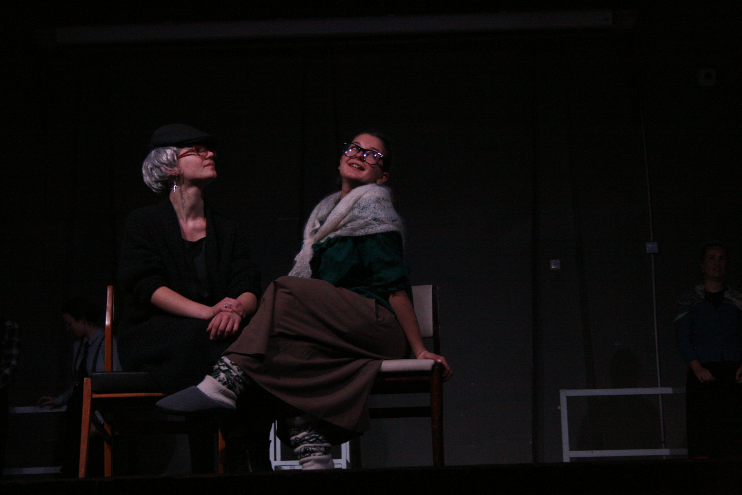 "Photo from the show ""The Chairs"". Two female actor sit on chairs, dressed like old ladies. One of them looks flirty or happily nostalgic"