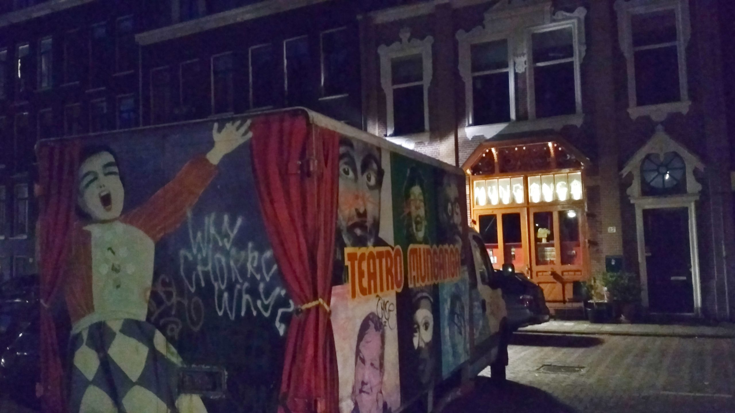 "A truck with the logo ""teatro munganga"" and images of 1900s theatre, parked outside of an Amsterdam house."