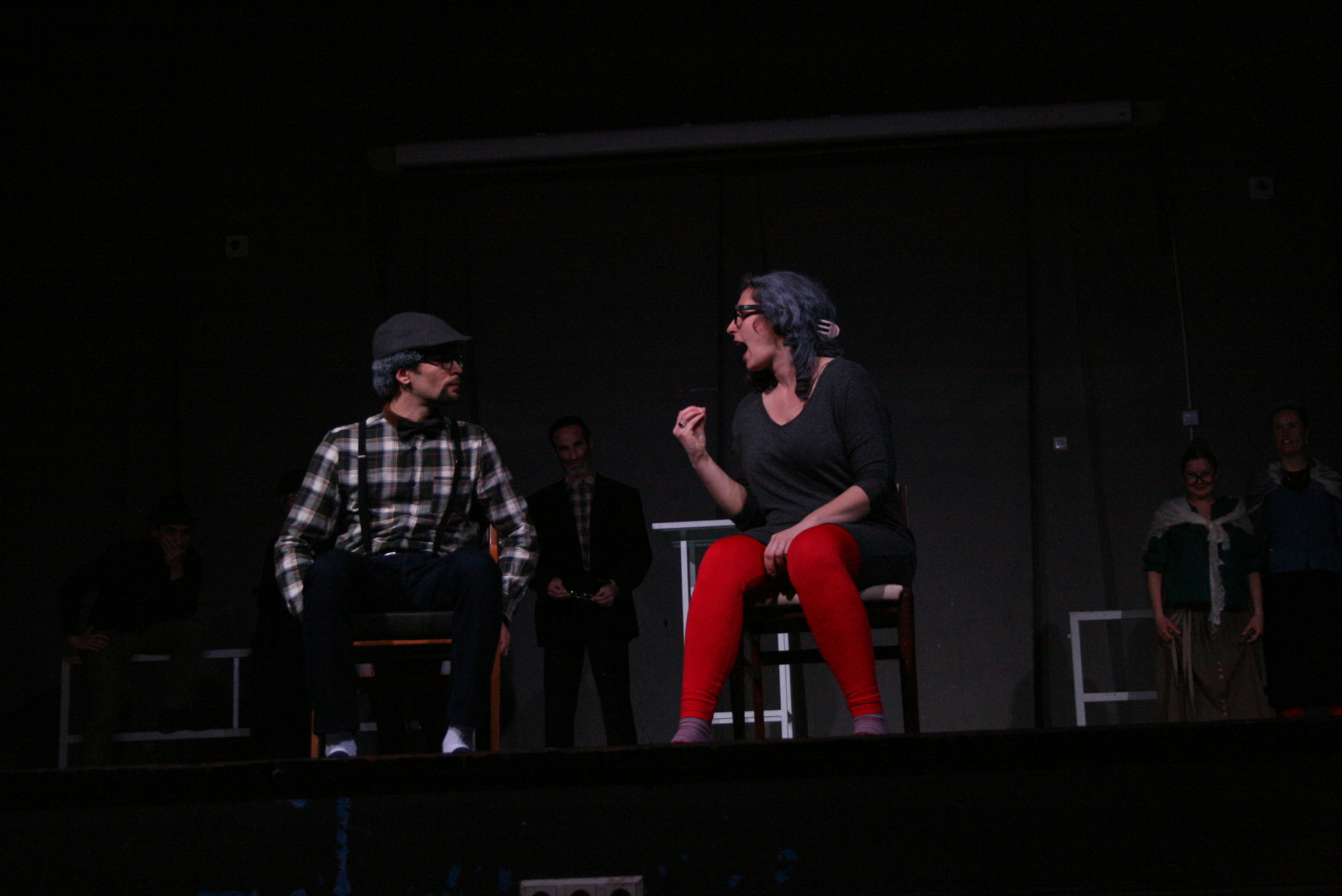 "Photo from the show ""The Chairs"". A male and a female actor sit on chairs. The female actor yells, clearly angry, at the male actor, who listens"