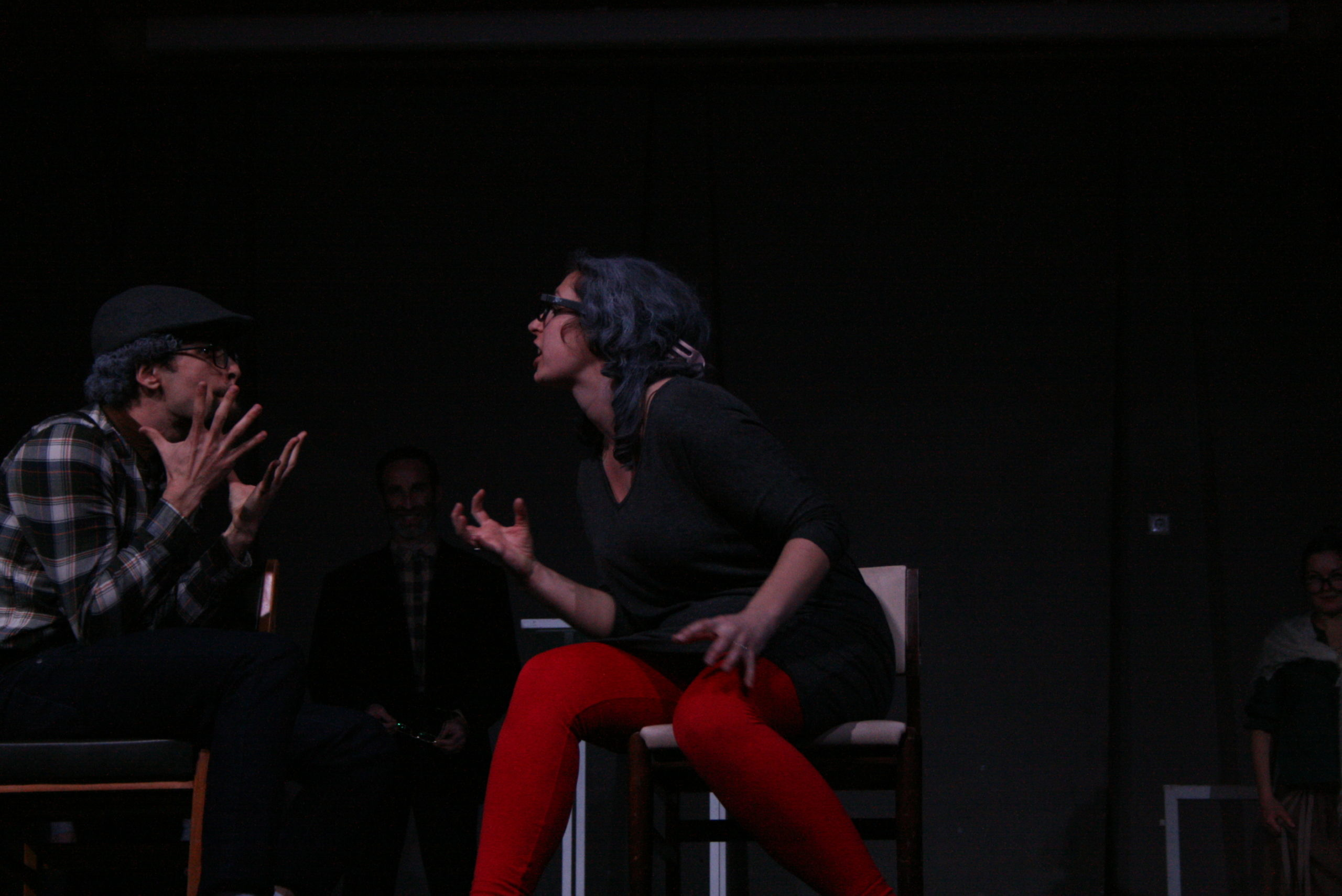 "Photo from the show ""The Chairs"". A male and a female actor sit on chairs, arguing. They are dressed in old-fashioned clothes"