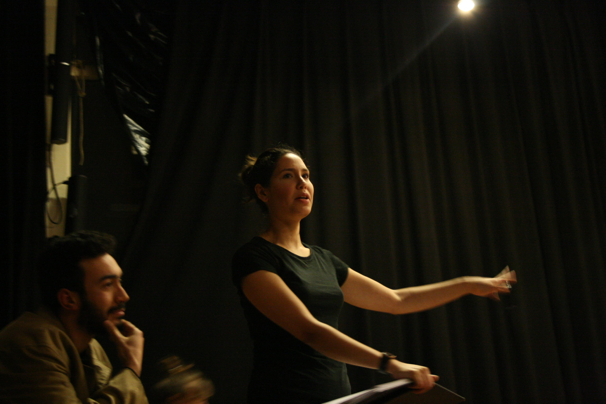 "Photo from the show ""Skin of our Teeth"". A female actor, probably backstage, waves at someone. At the left of the photo, behind her, a man, touching his chin."