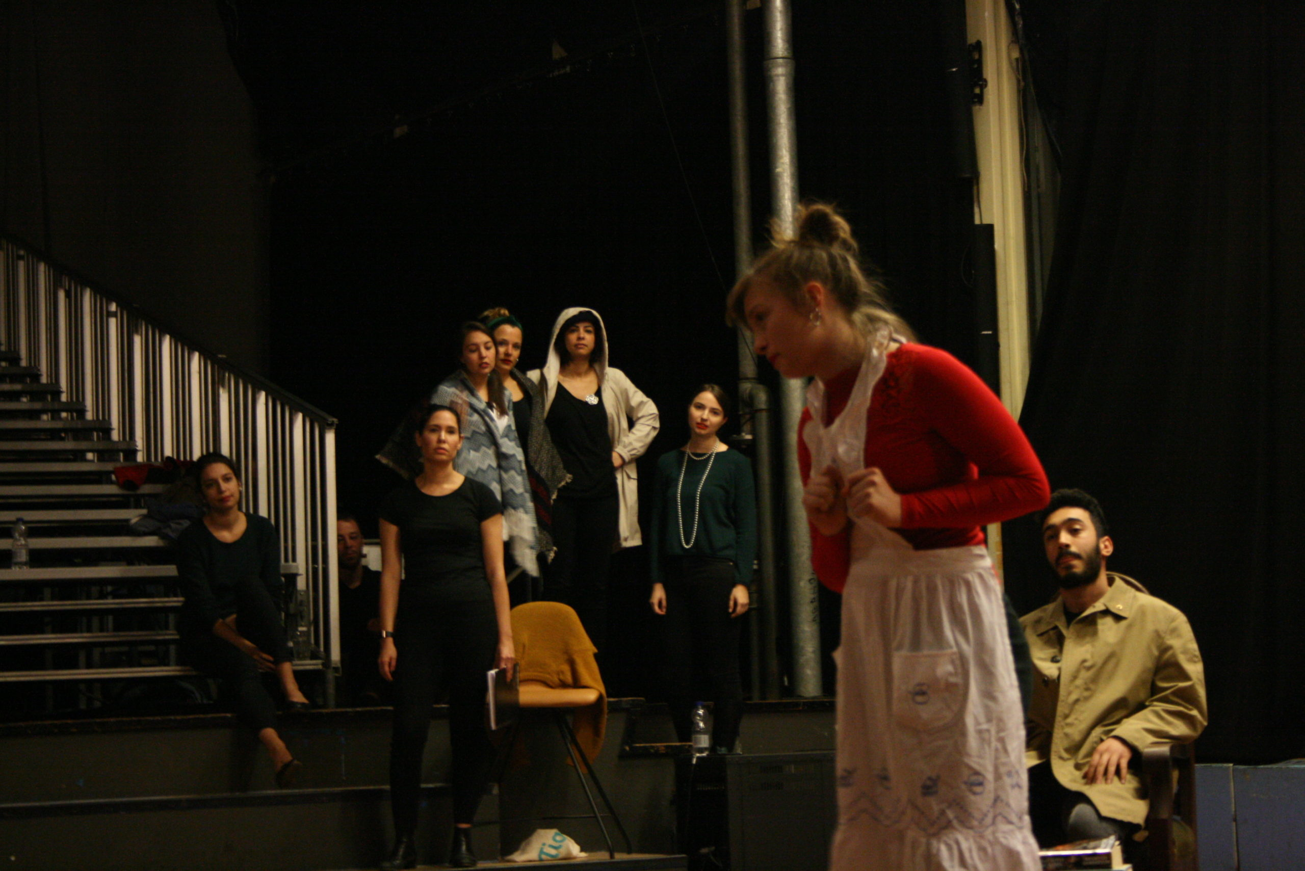 "Photo from the show ""Skin of our Teeth"". A female actor dressed like a maid on stage, her hands clenched in fists and on her chest. Behind her is the rest of the cast, looking at her"