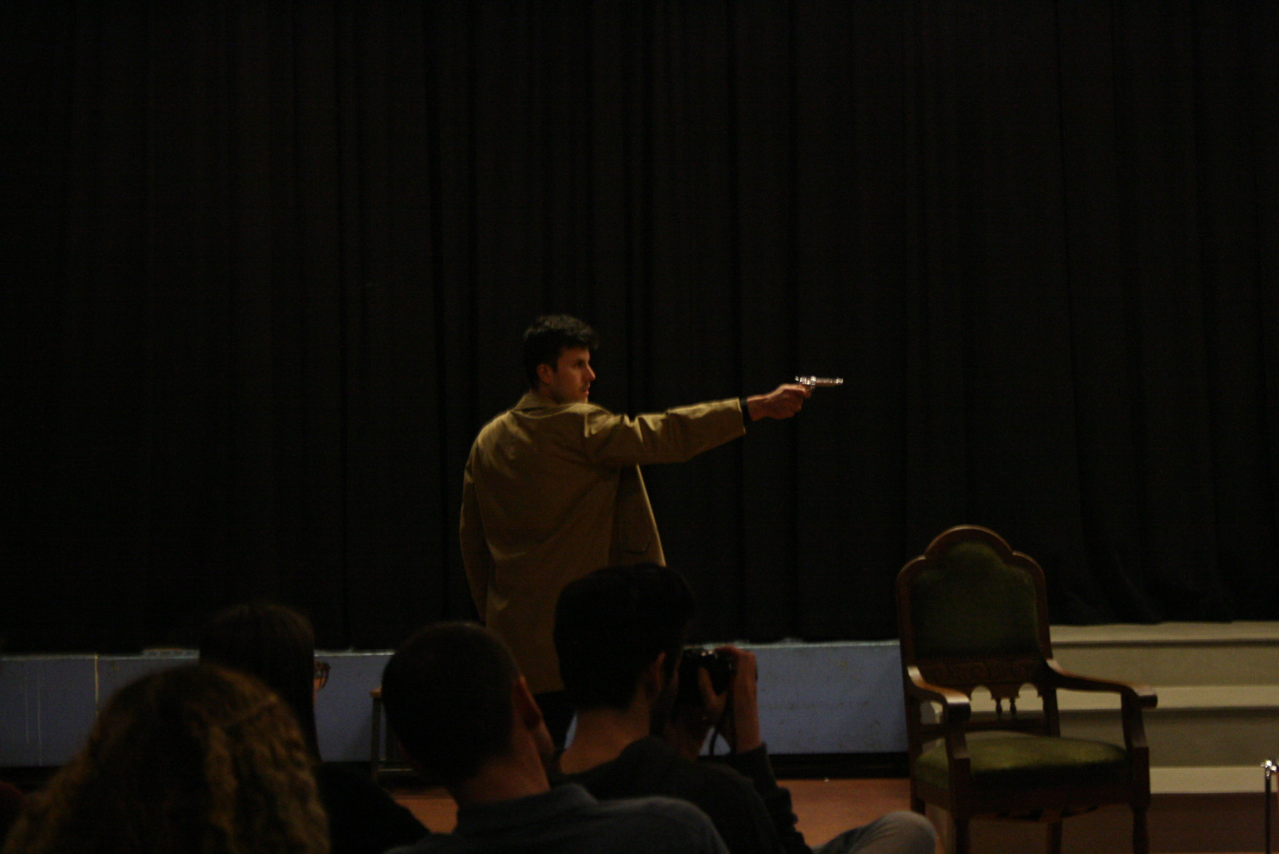 "Photo from the show ""Skin of our Teeth"". Man with half-long beige coat is pointing the gun at someone out of the picture"