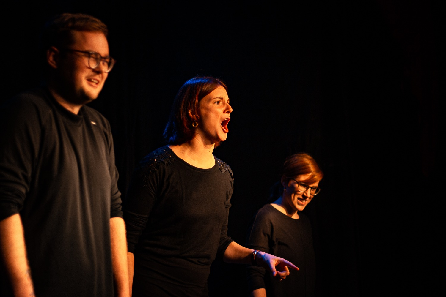 Act Attack's improv and physical show. Three people on stage wearing black. Two women, one man. The middle woman yells, the man cries
