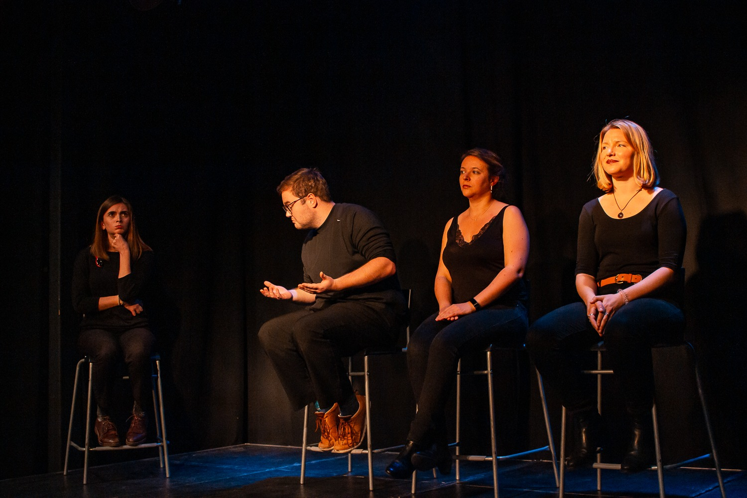 Act Attack's improv and physical show. A group of people on stage wearing black, sitting on bar stools. Three women and a man making a gesture like he's wondering