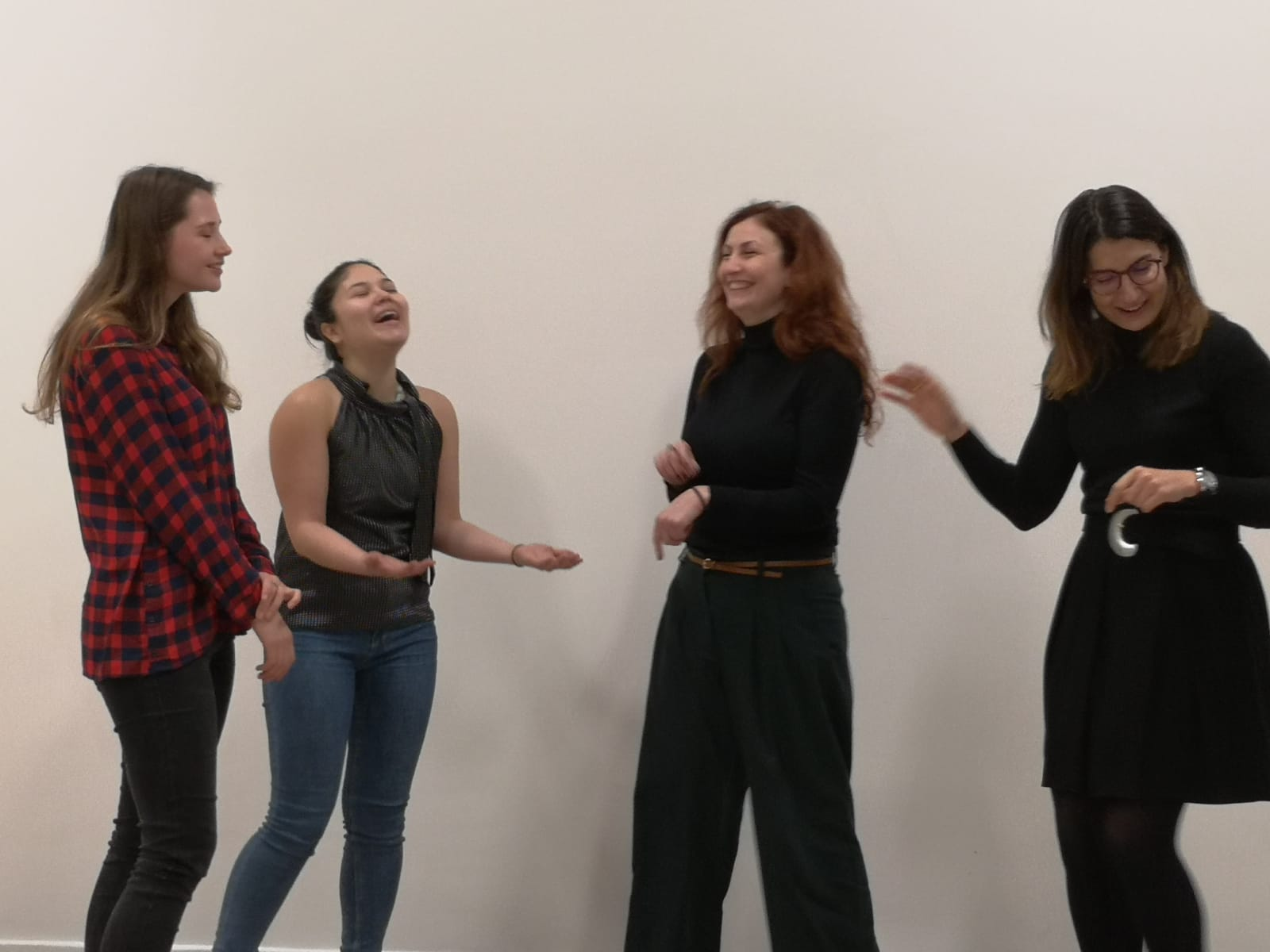 Acting class Act Attack. Four women are standing next to one another, moving their arms and laughing