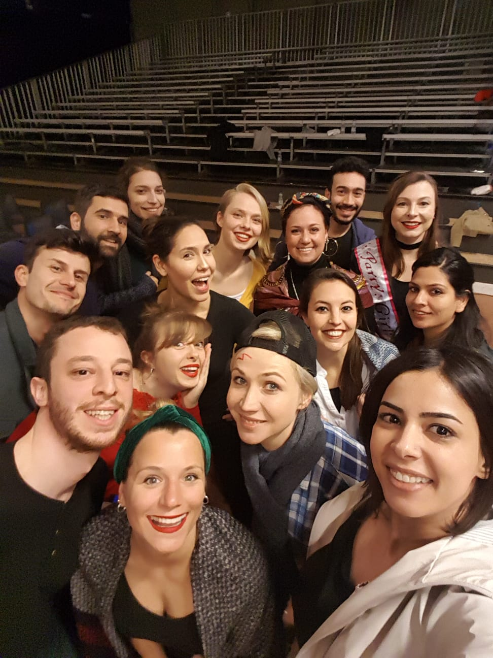 "Photo from the show ""Skin of our Teeth"". Fifteen people take a group selfie in front of the stands"