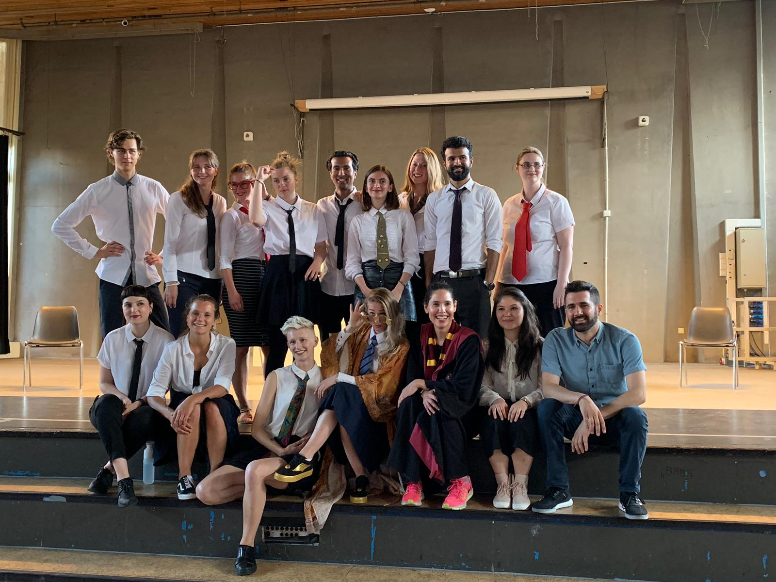"From the rehearsal of the show ""the magic school"". A group of people pose for the picture. Most of them wear a white shirt and tie"
