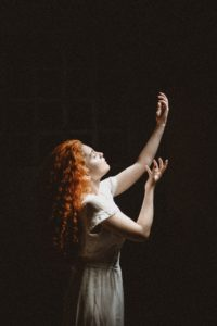 girl in white dress, with long, red, curly hair is performing in theater. Her arms are reaching up. Dark background