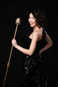 Beautiful young female vocalist in shiny black evening dress holding golden vintage microphone, playful smile, preparing to sing during a musical show