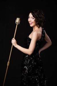 Beautiful young female vocalist in shiny black evening dress holding golden vintage microphone, playful smile, preparing to sing during musical show