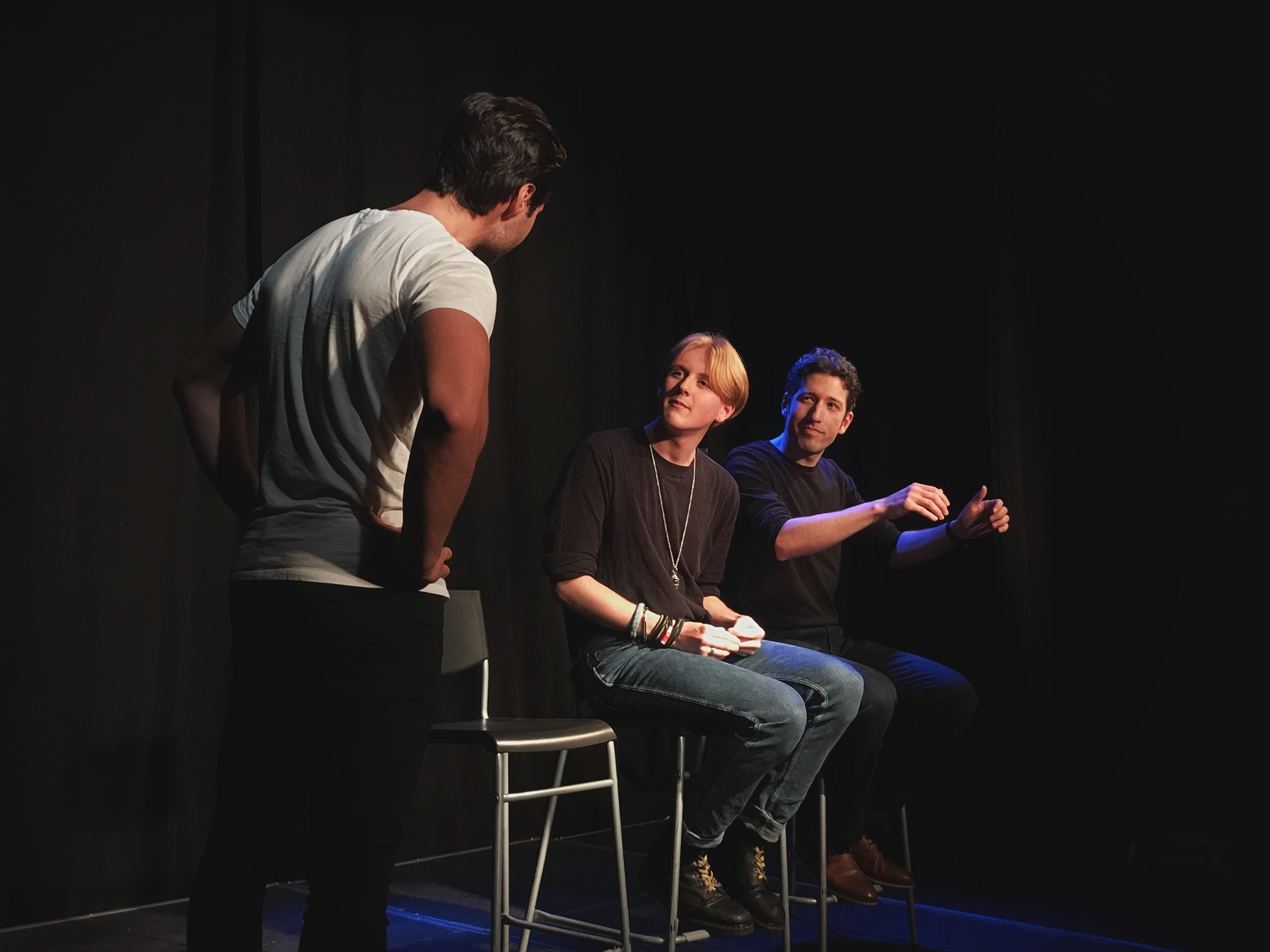 Act Attack's Pure Improv show. Two men sit on bar stools. One of them pretends to drive, the other one looks at a third man, who is standing
