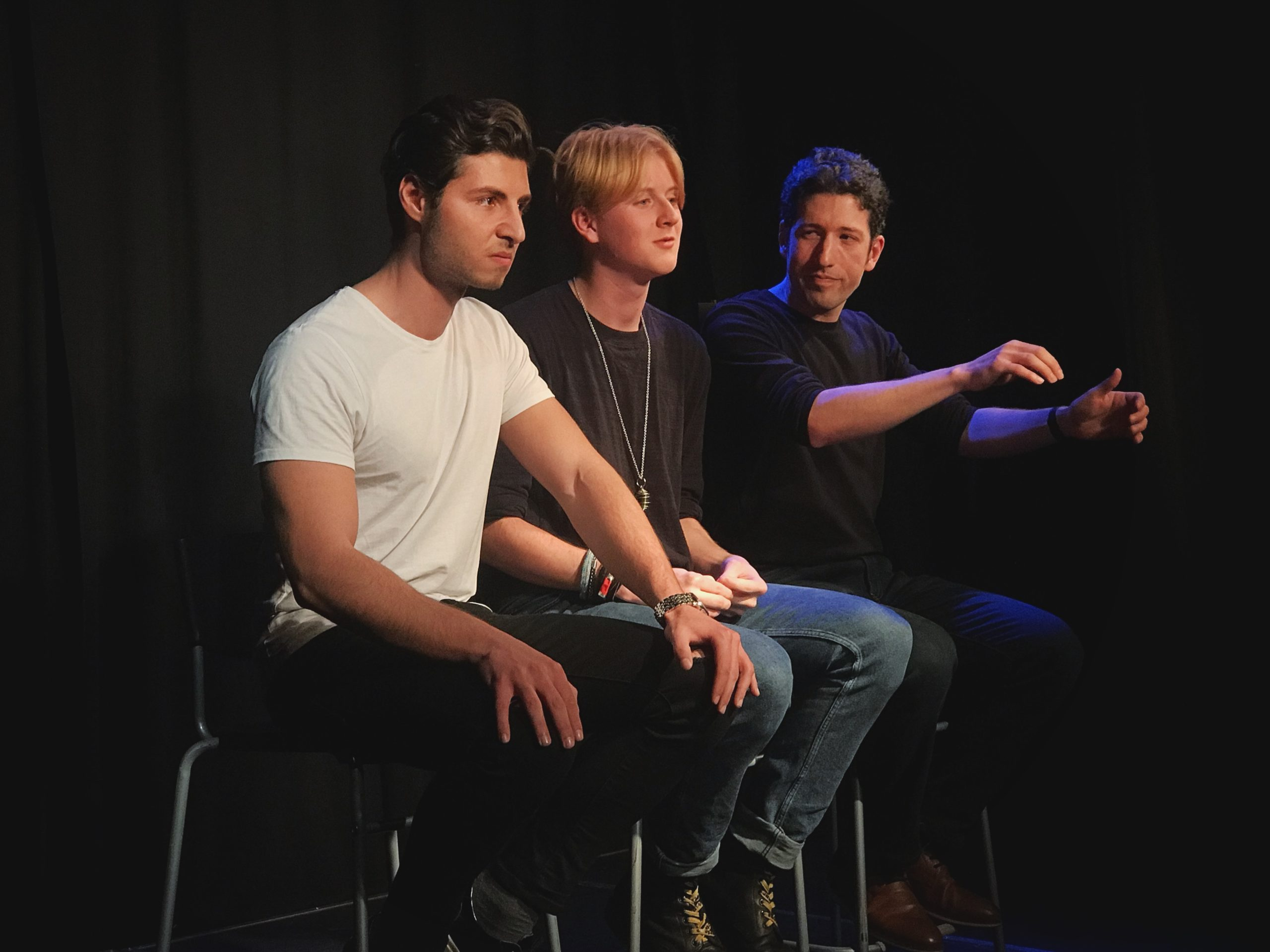 Act Attack's Pure improv show. Three men sit on bar stools. One of them pretends to drive