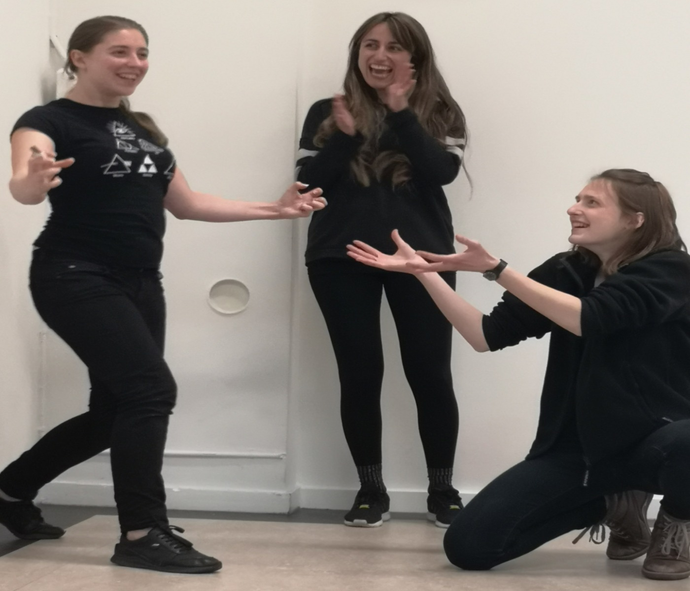 Three Act Attack's students are practicing. They are three women wearing black clothes. They are all laughing. Two stand, of which one is clapping, and the other is walking with open arms. The third is kneeled while reaching out towards her walking mate.